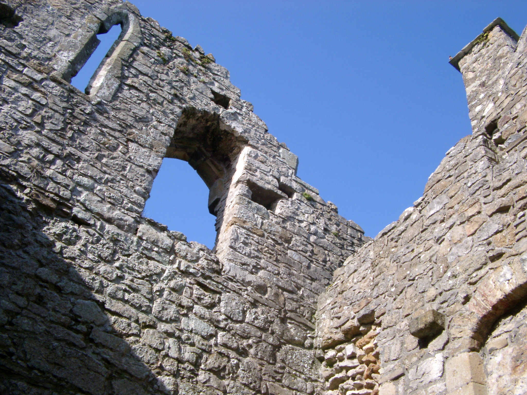 Old stone wall with window openings in a ruined building, low angle looking up against blue sky