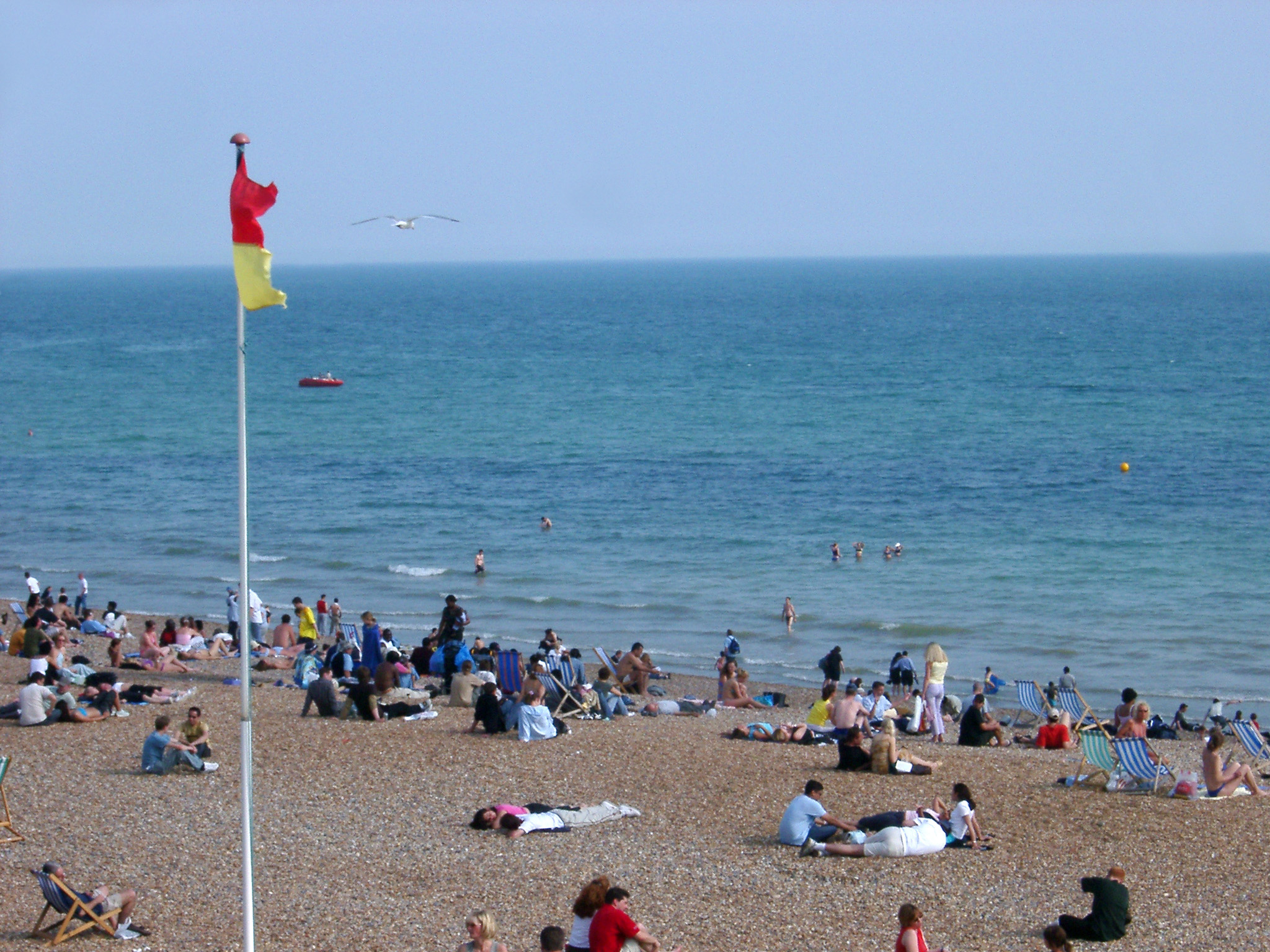 Tourists Relaxing at Beautiful Brighton Beach in England.