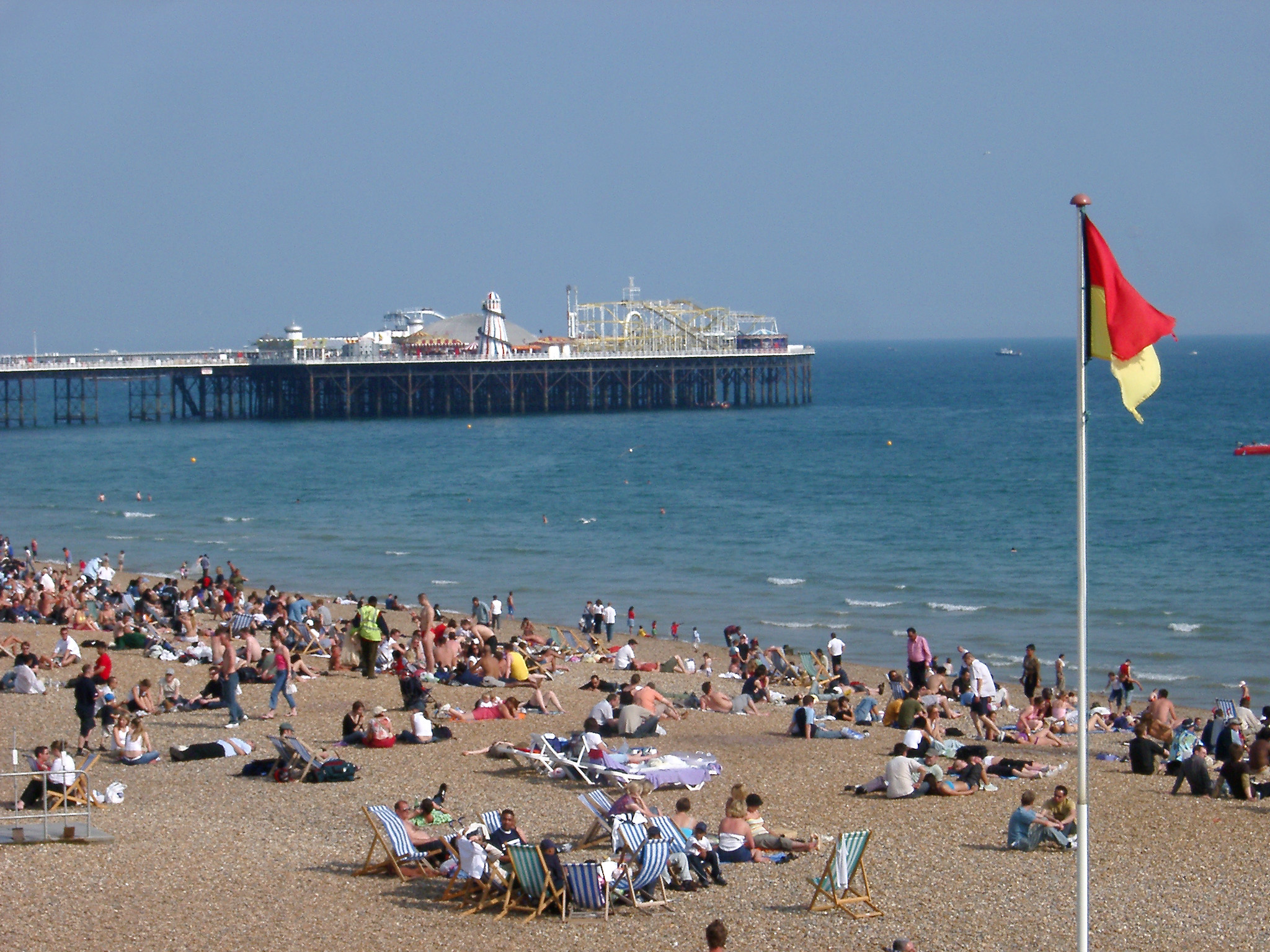 Tourists Relaxing at the Seaside Near the Famous Brighton Pier, also known as Palace Pier, Located in England.