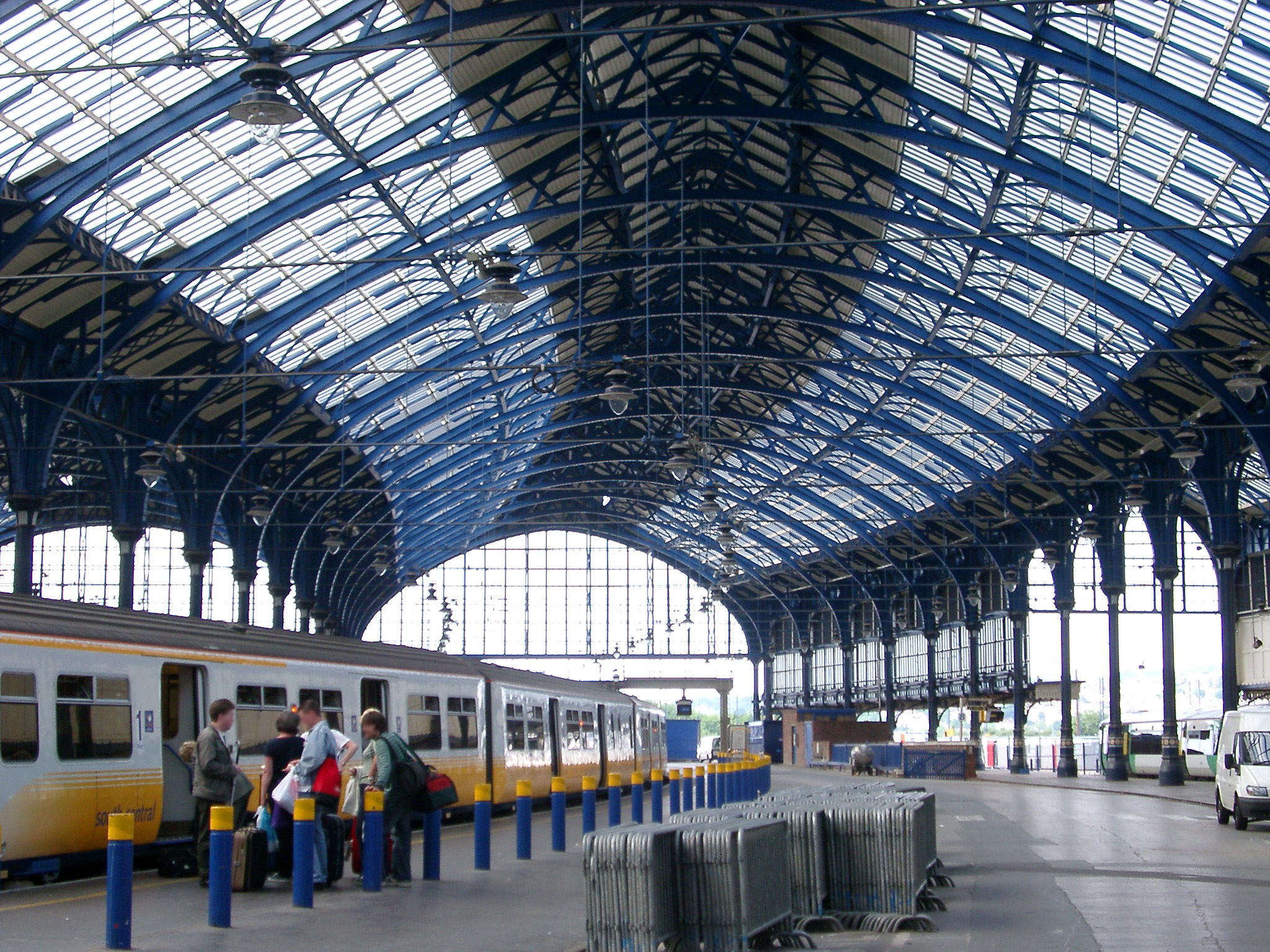 Interior of Brighton Station with its curved glassed roof and a train standing at the platform with visitors boarding