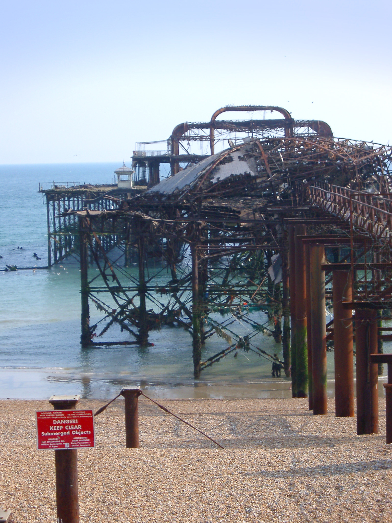 Fire damaged ruins and mangled warped iron structure of the old Brighton Pier , a Victorian landmark