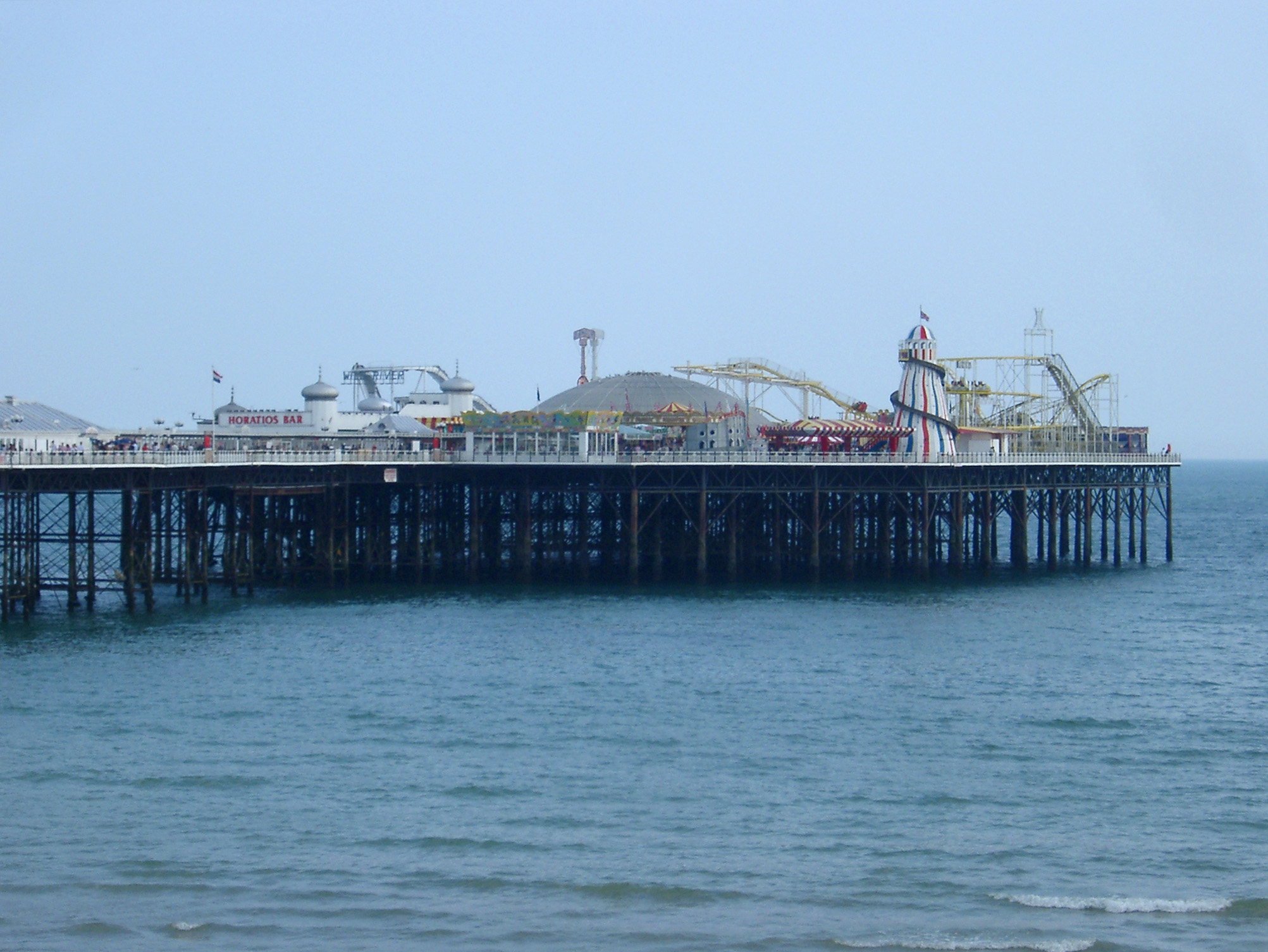 View across the water of the Brighton Pier with its historical buildings now housing an amusement park and popular tourist attraction
