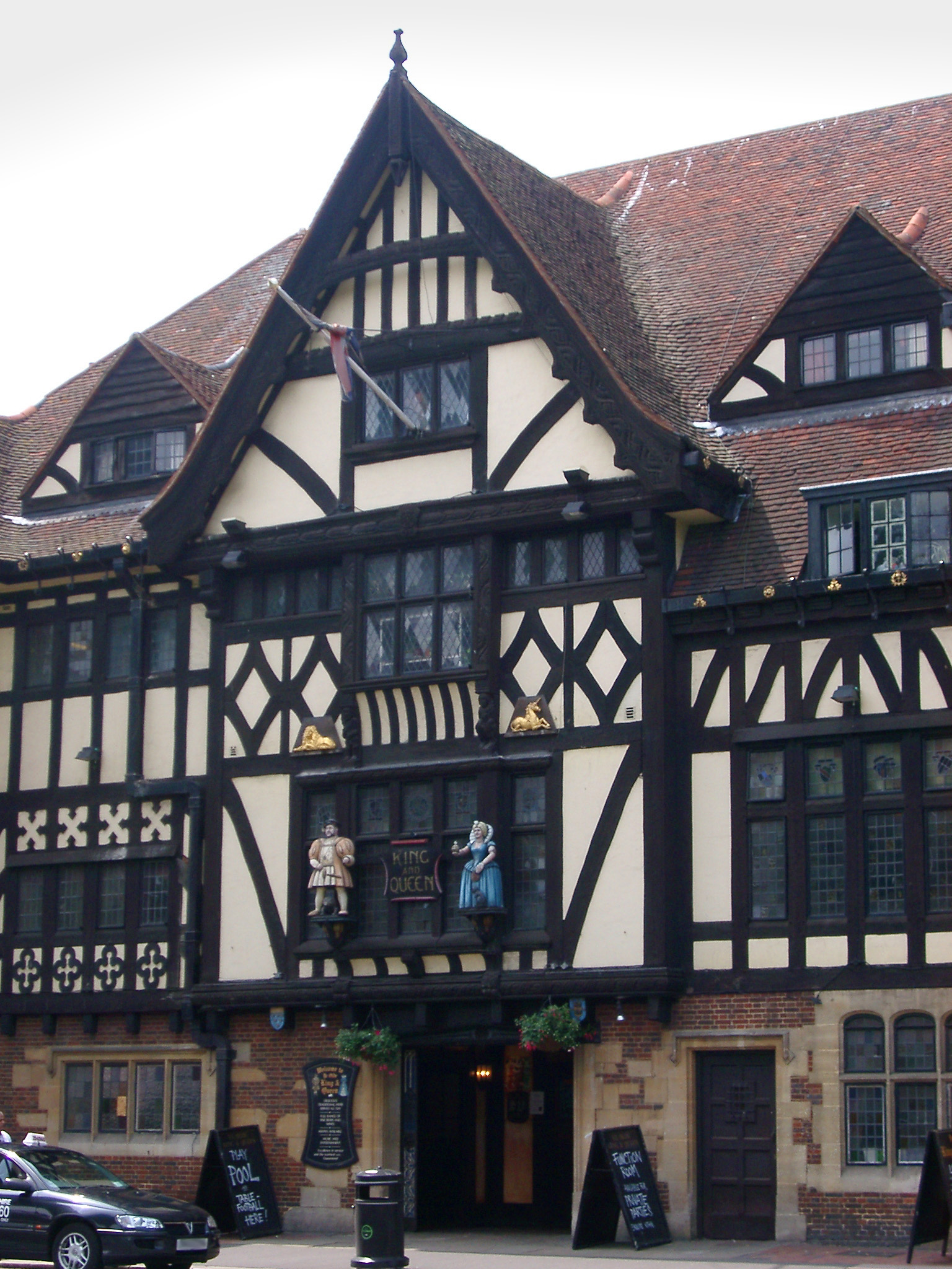 Tudor frame pub facade showing the traditional exterior timber framework on  the white walls with two