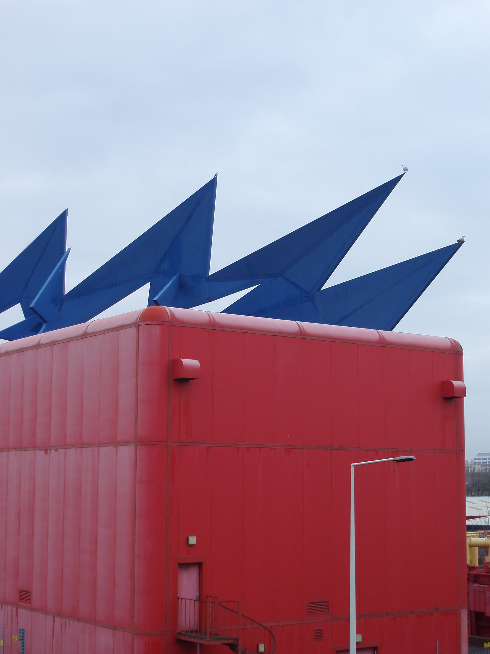 Contemporary art on a powerbox substation in the docklands in Cardiff Bay, Wales with a colorful blue zigzag electric spark icon mounted over a red electricity substation