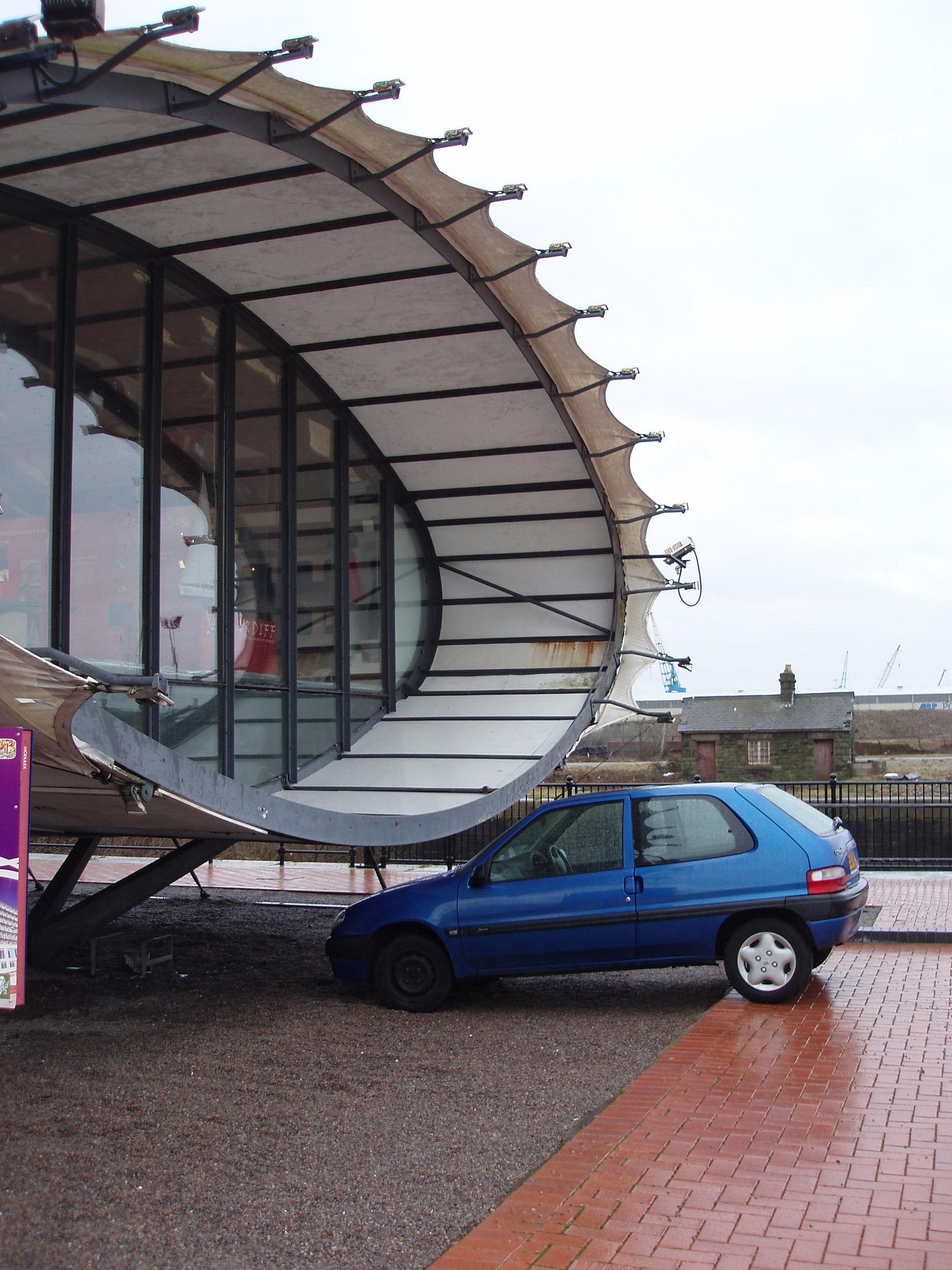 Blue Small Car at Famous Architectural Cardiff Bay Visitor Centre Tube at Cardiff Bay, Wales.
