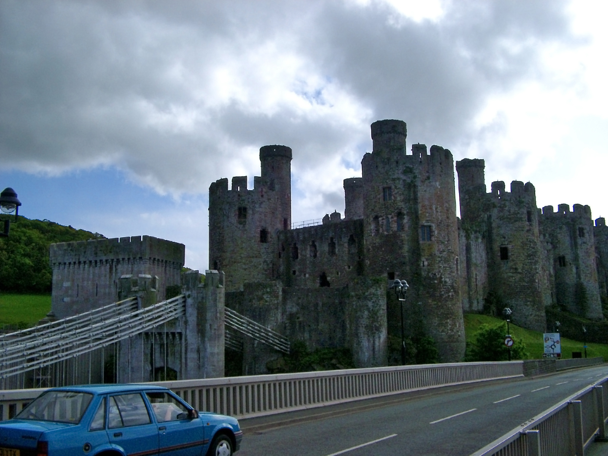 Blue Car Passing the Bridge Near the Historic Conway Castle, Located in Wales.