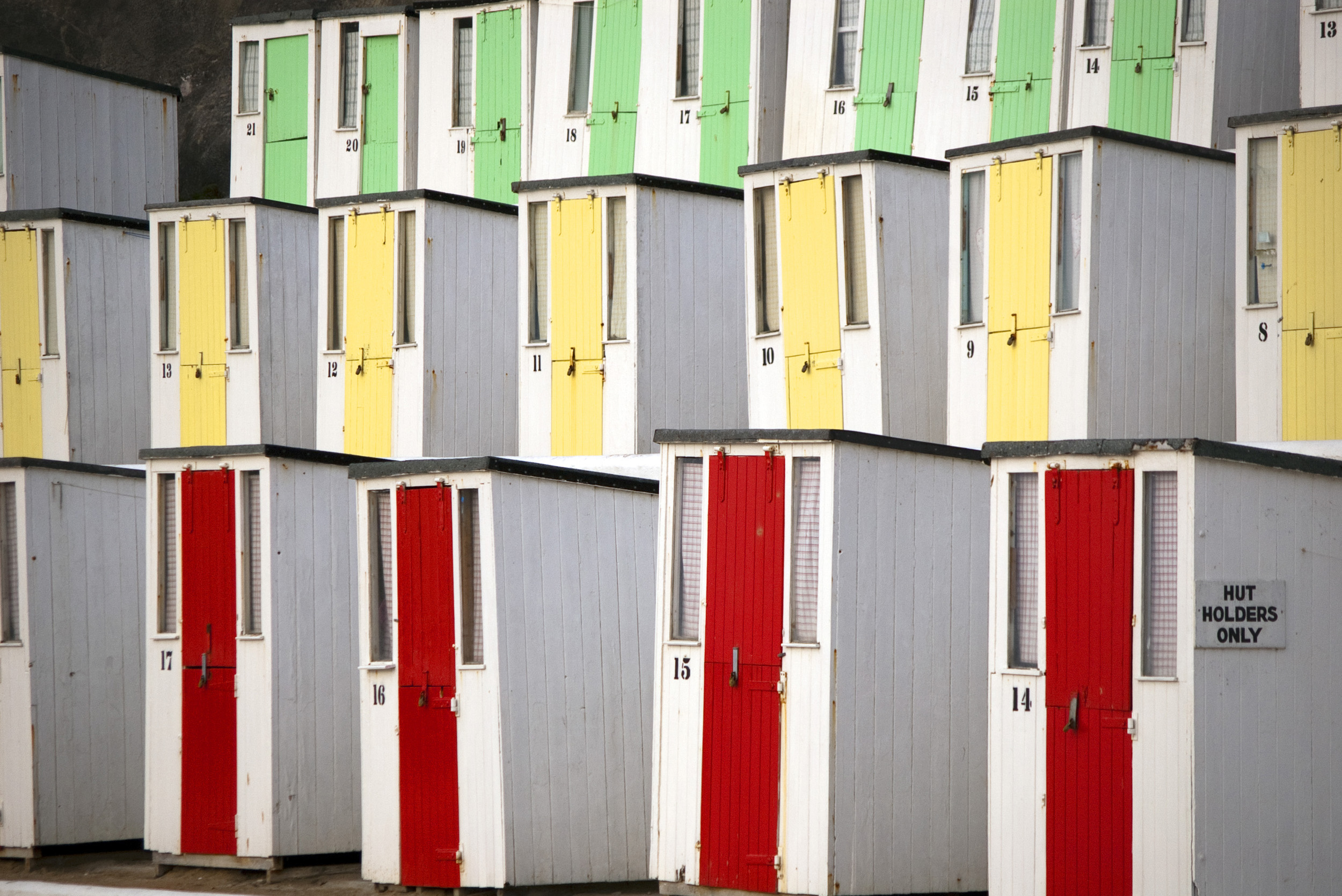 rows of beach huts at newquay with brightly painted doors