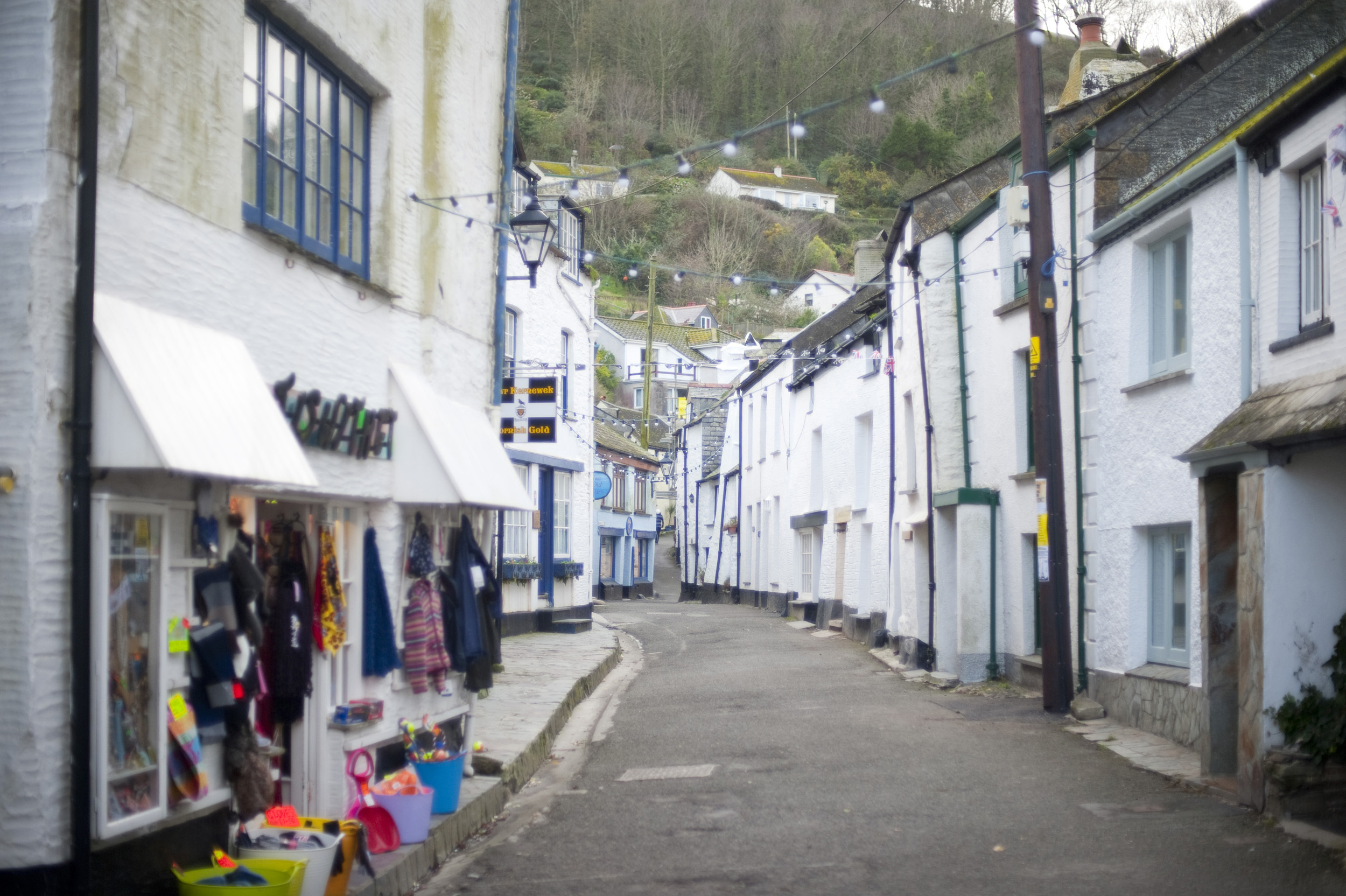 narrow street of white painted rustic built houses in polperro an unspoilt cornish fishing village