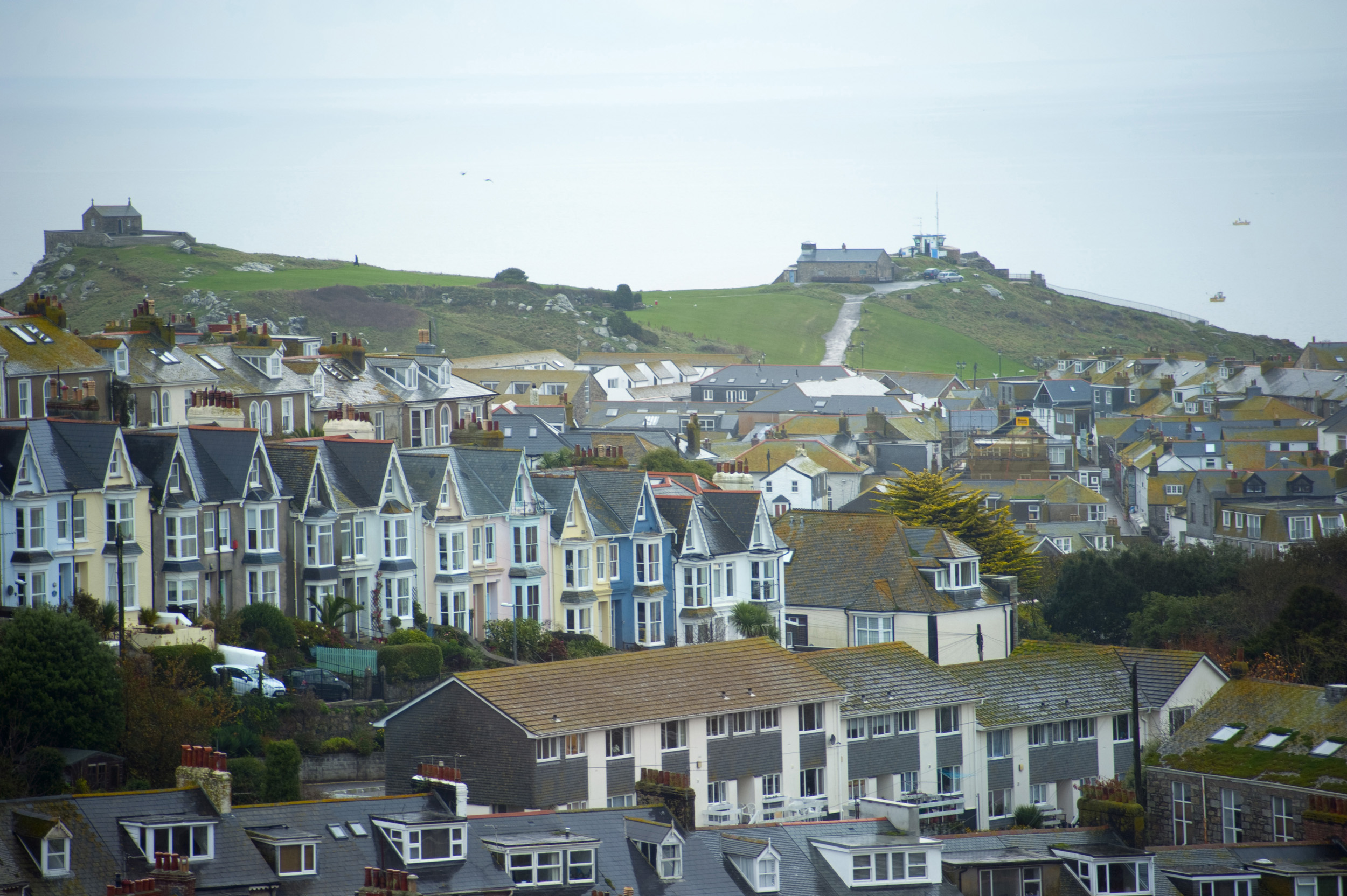 rows of old and new houses in the cornish town of st ives, Chapel of St Nicholas and the watch station in the distance on a part of town known as The Island