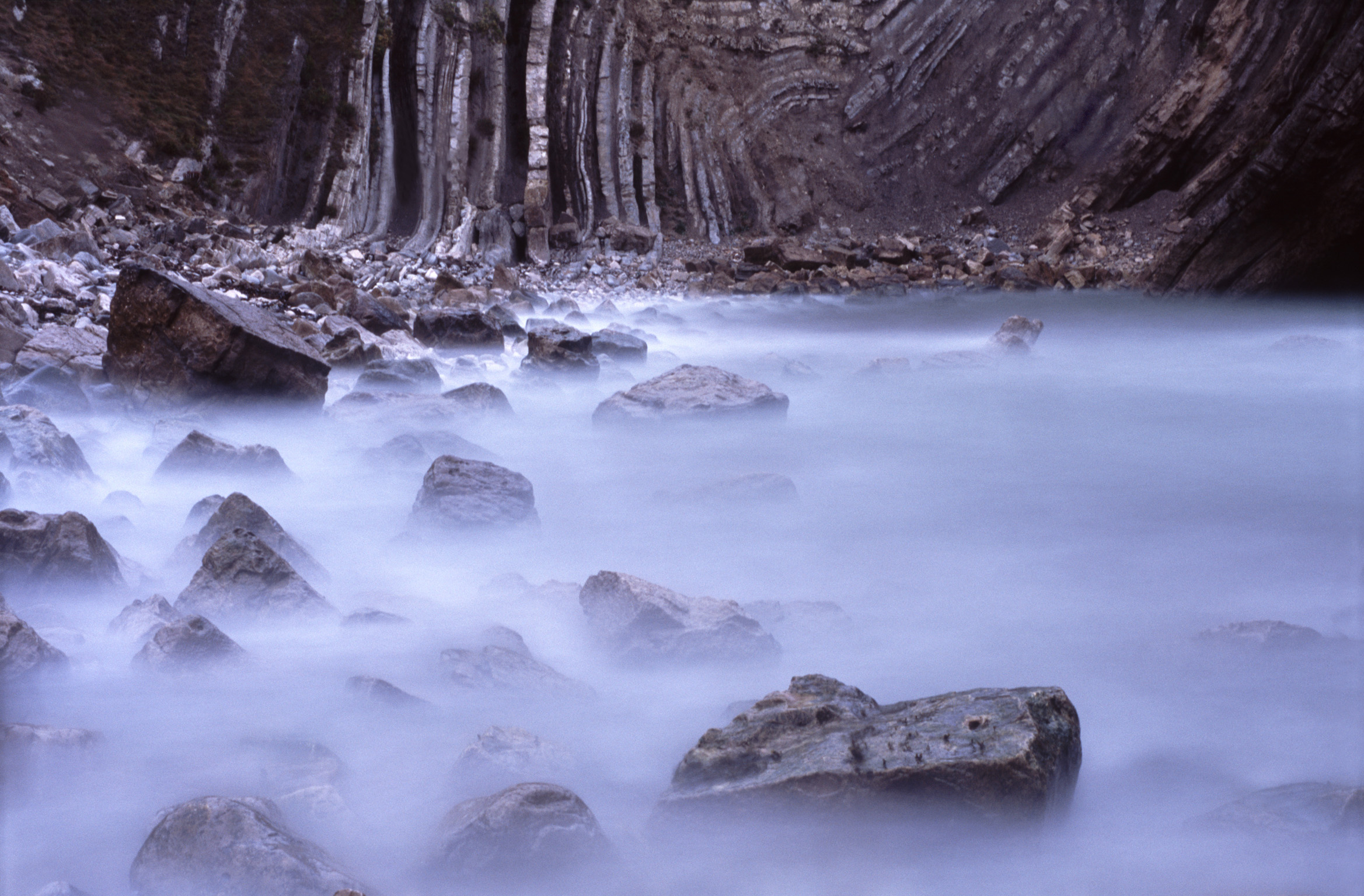 long exposure image of water lapping rocks in stair hole, dorset.
