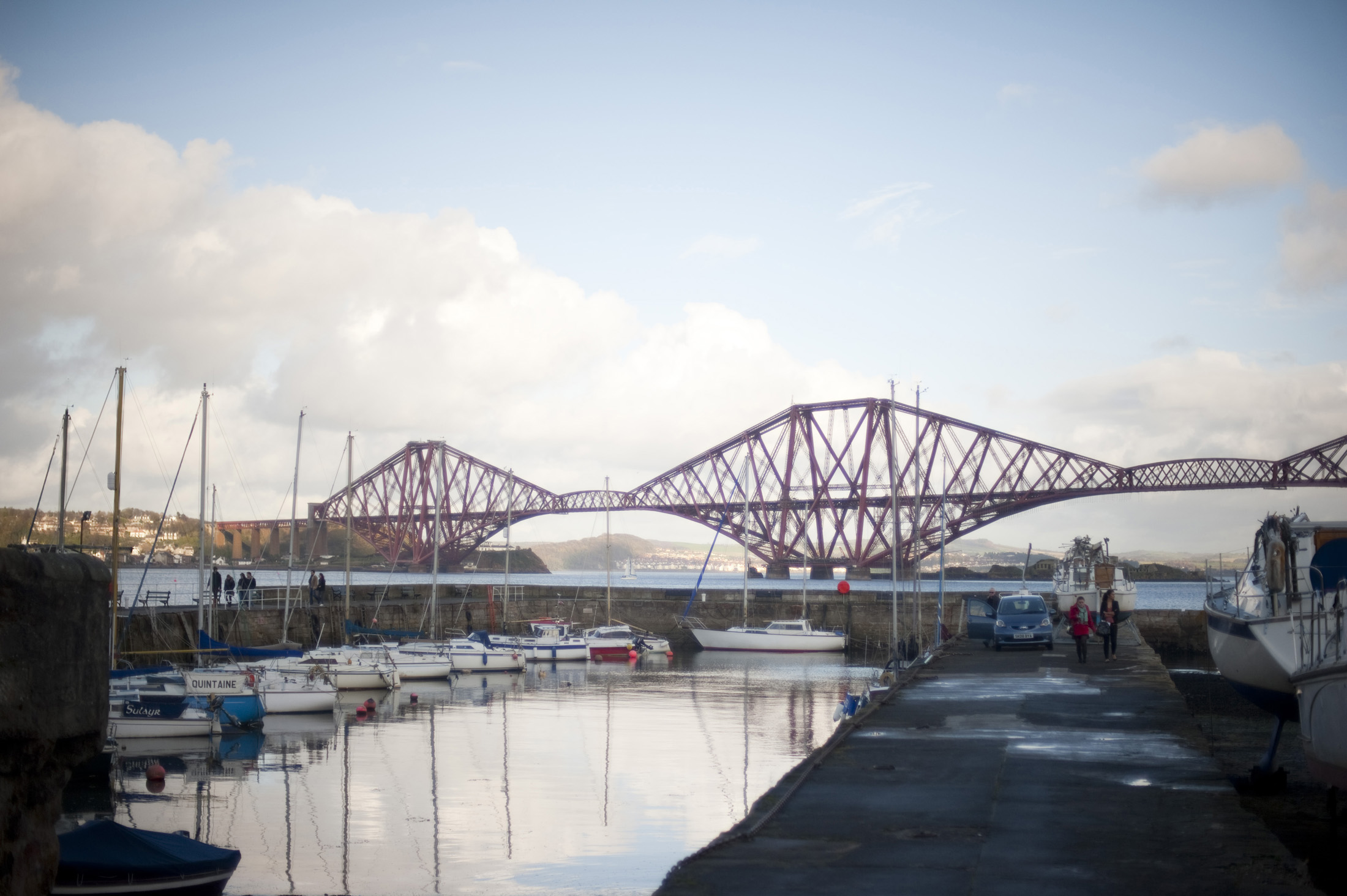 boats in the harbour with the iconic forth rail bridge in the background, queenferry, scotland