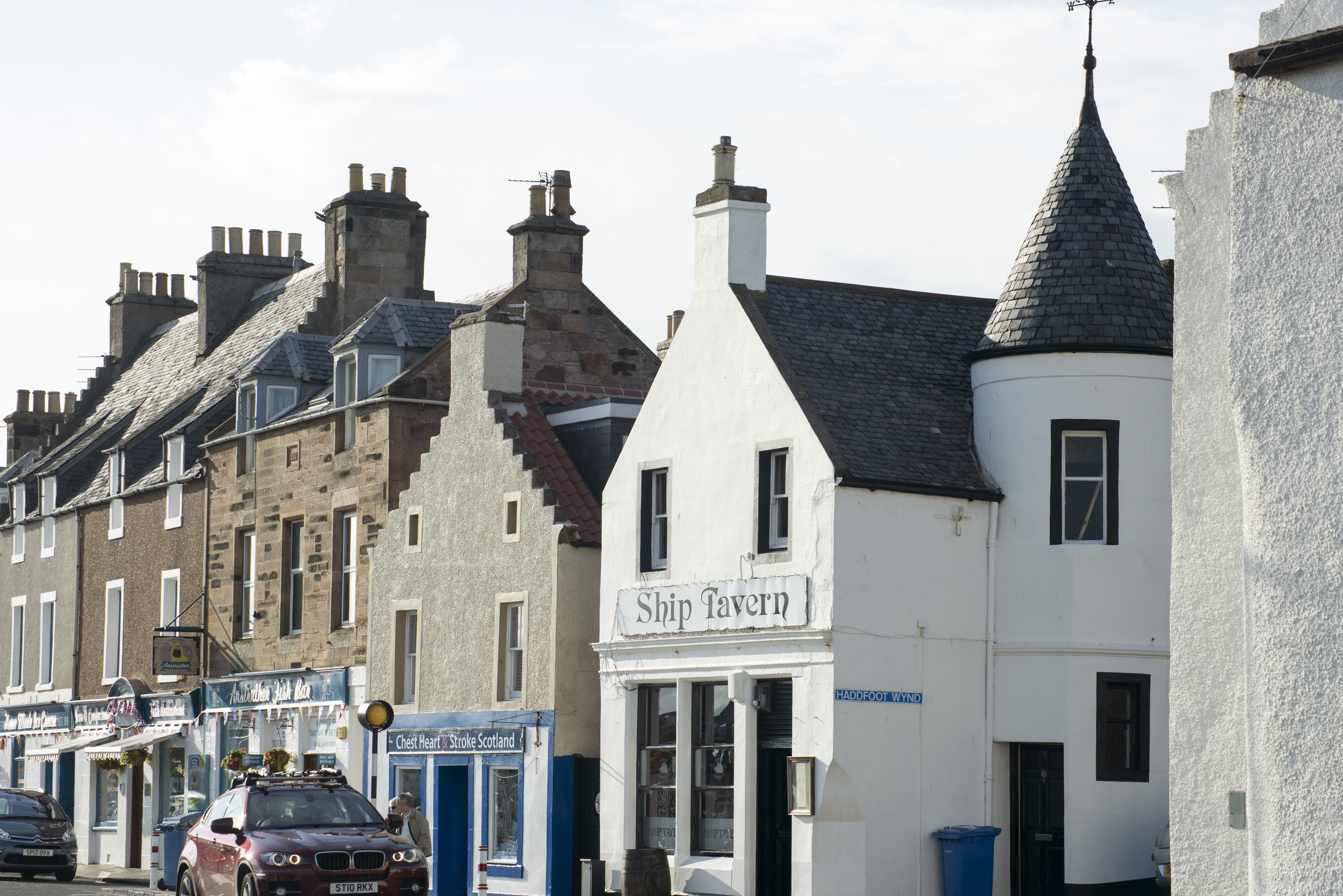 Cars parked in front of row of quaint traditional homes and storefronts in Anstruther, Scotland