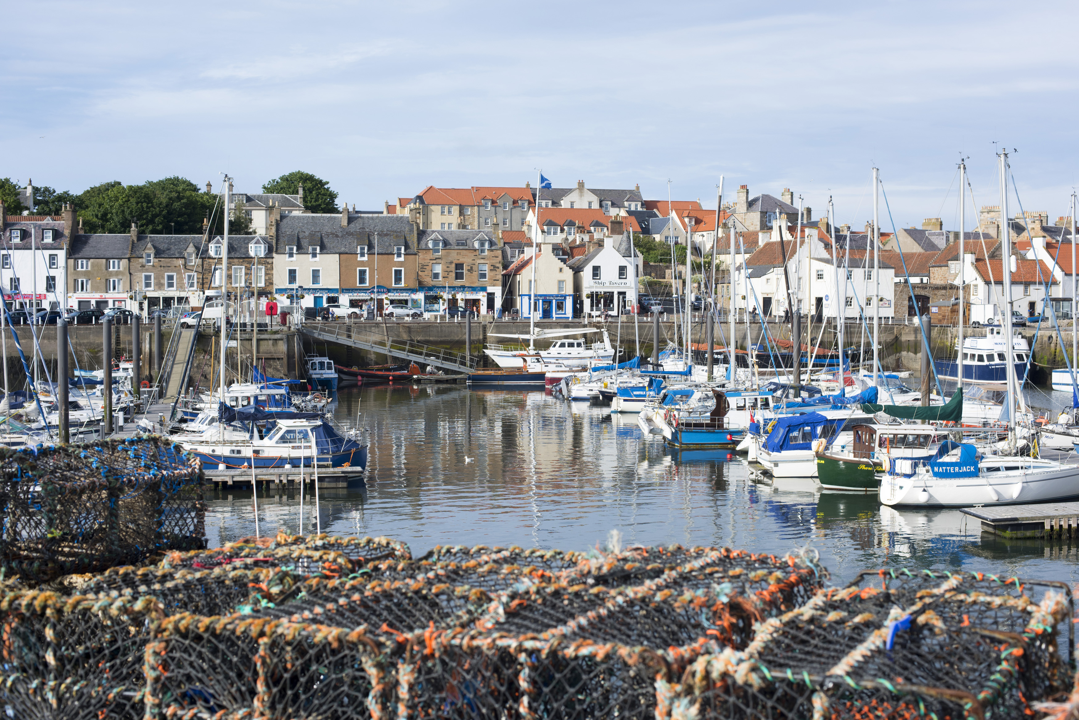 wire fishing traps with fishing and pleasure boats and yachts moored in the harbour overlooked by waterfront houses, Anstruther, Scotland