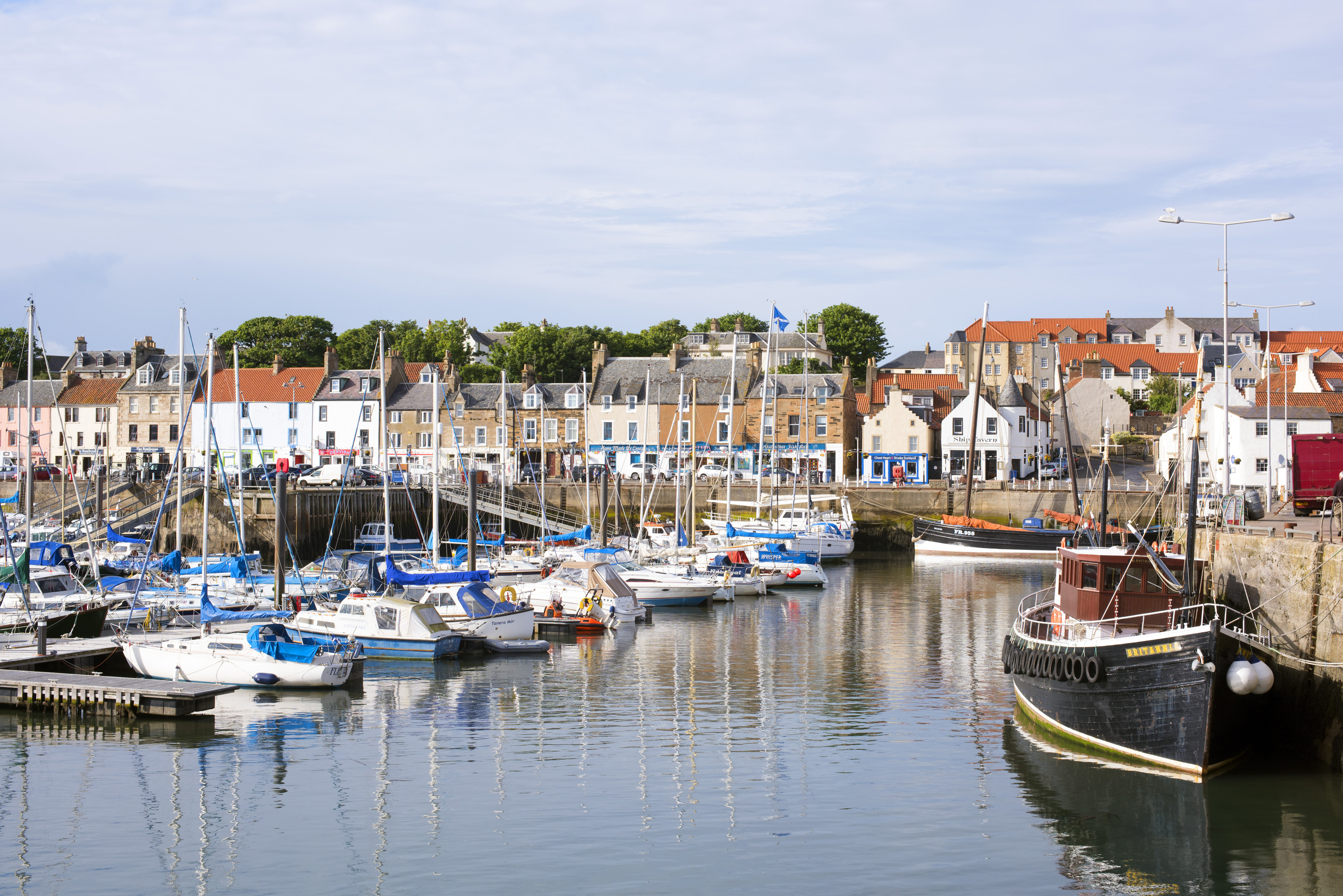 Picturesque view of a tranquil Anstruther harbour on the Fife coast in Scotland with moored yachts, pleasure and fishing boats