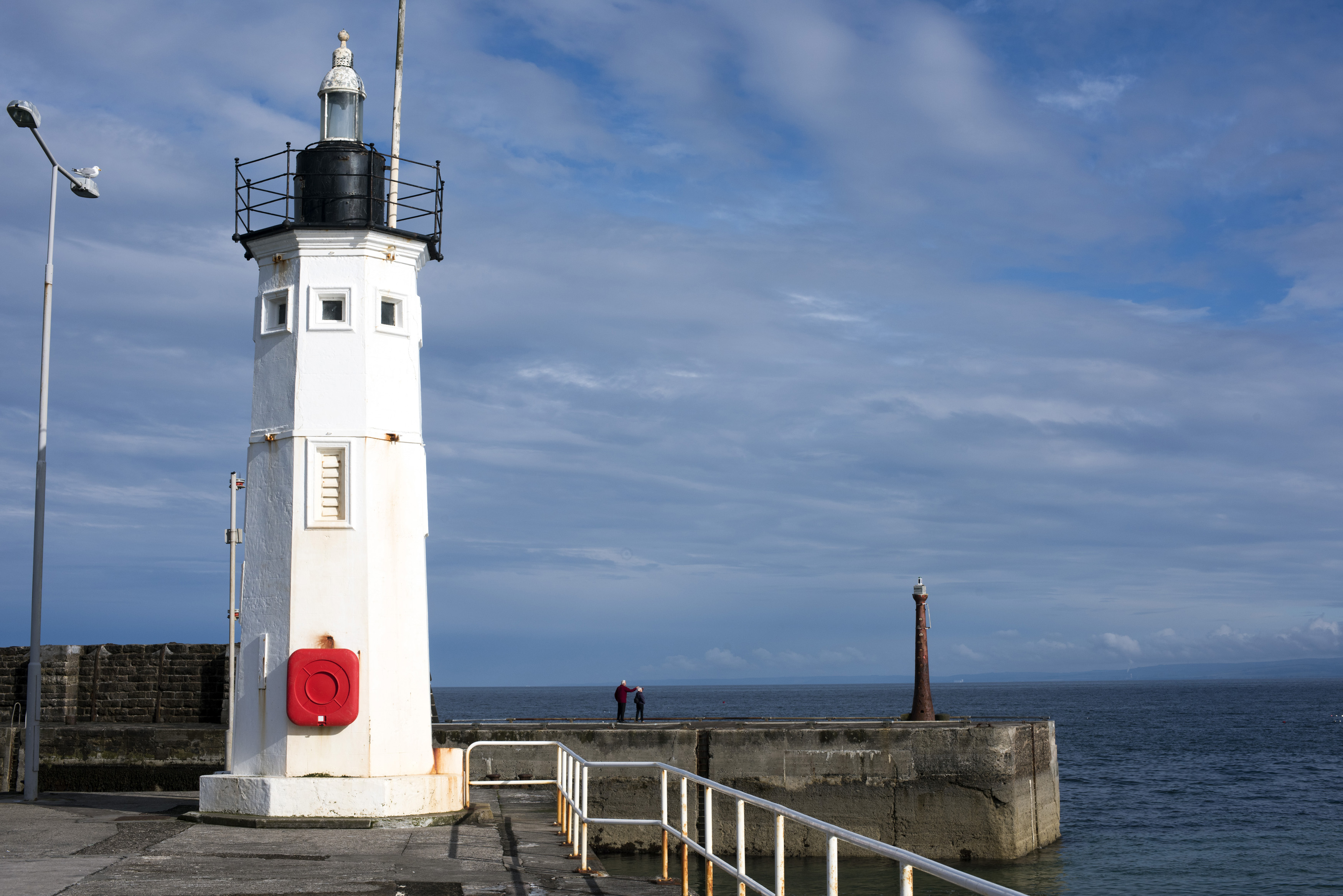 Picturesque white lighthouse, Anstruther, Scotland on the seawall at the entrance to the harbour with copy space on a blue sky