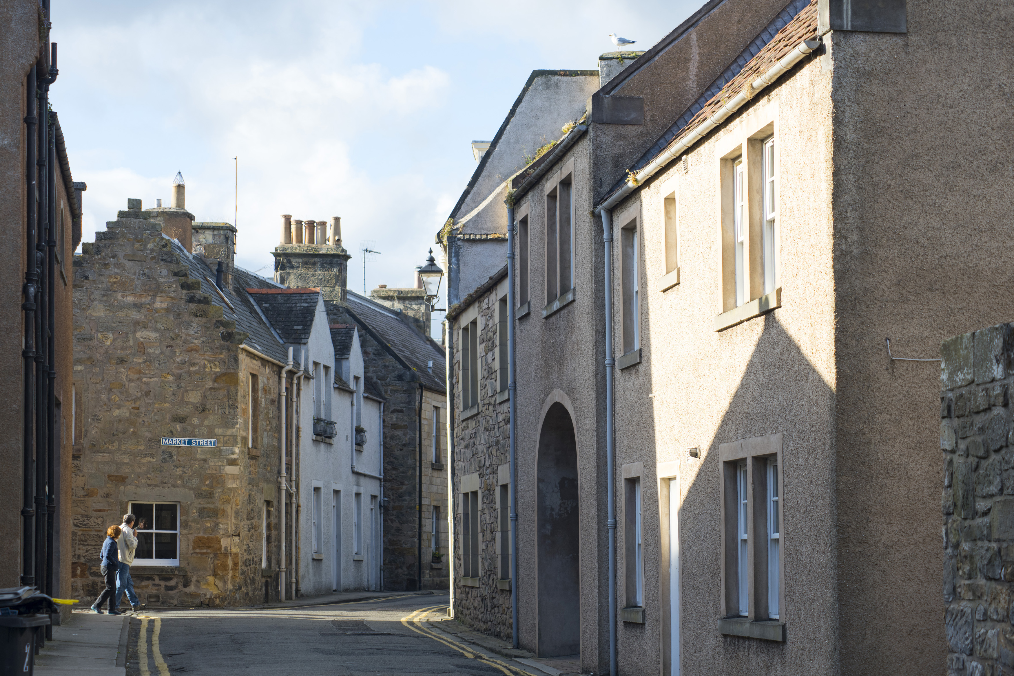 Two people walking through a narrow back street past historic cottages and townhouses, St Andrews, Scotland