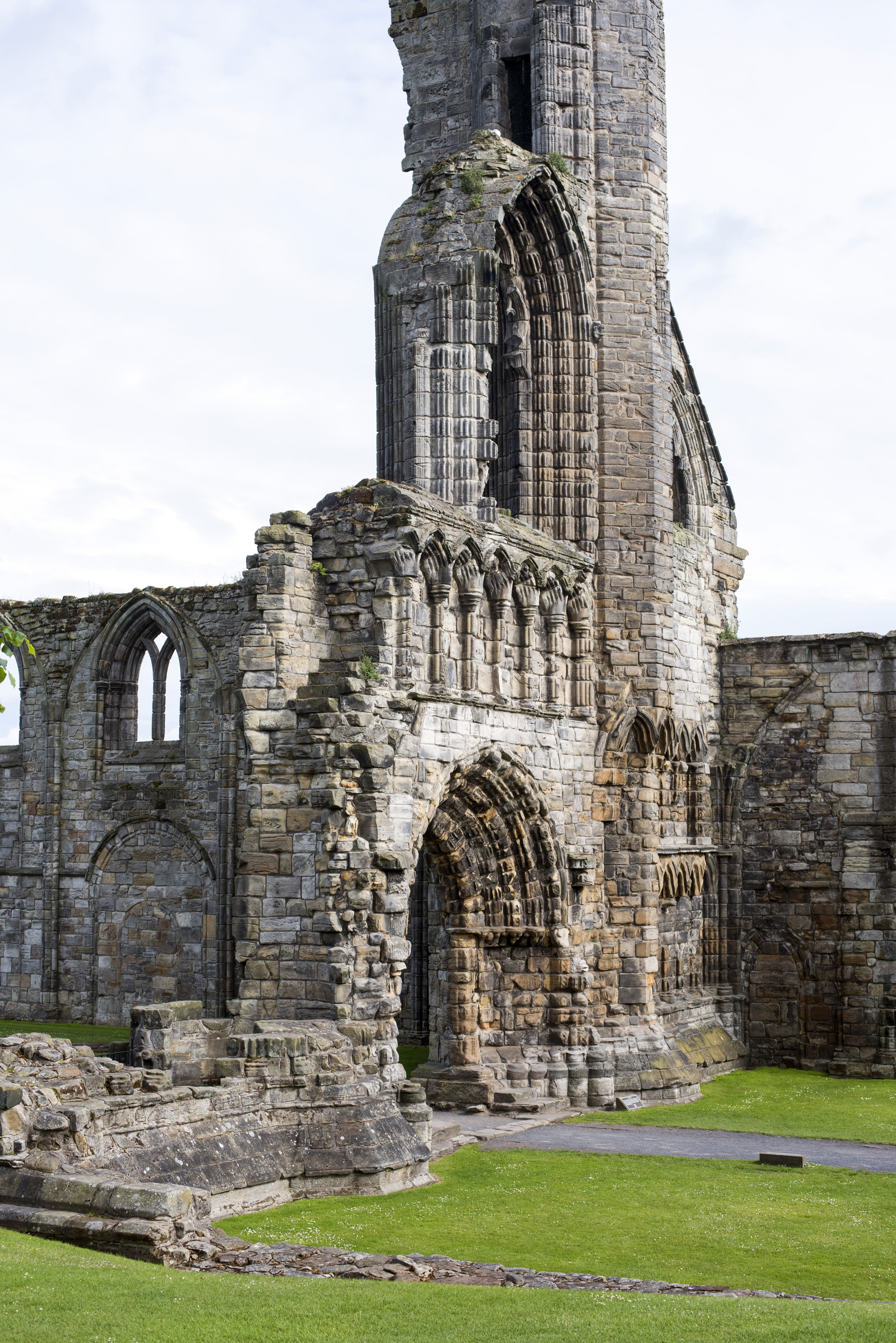 Graceful Gothic stone arches and remnants of wall in St Andrews Cathedral ruins, Scotland against a grey sky with copy space