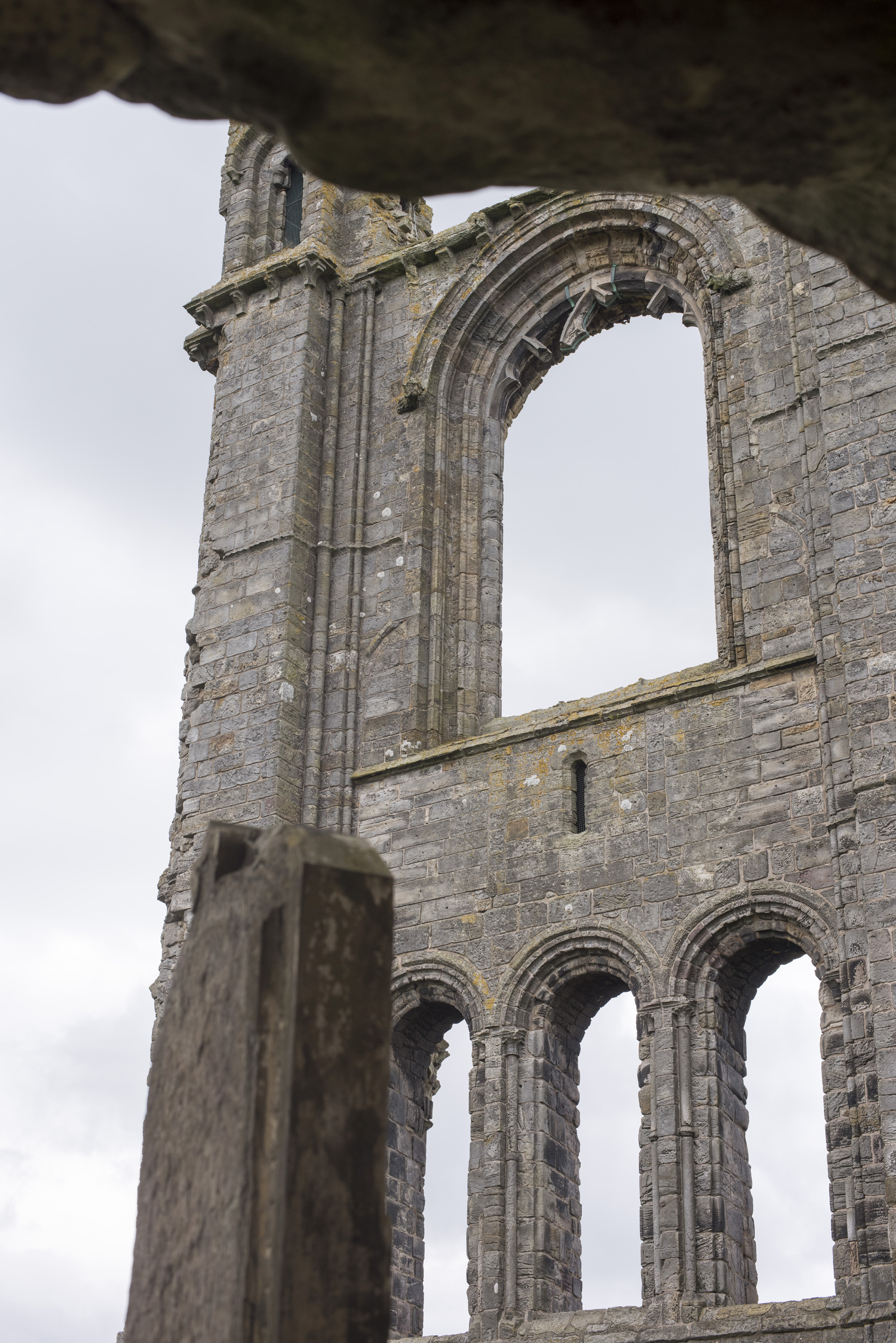Detail of the St Andrews Cathedral ruins, Scotland showing the arched gothic windows in an ancient stone wall with view through to a hazy sky