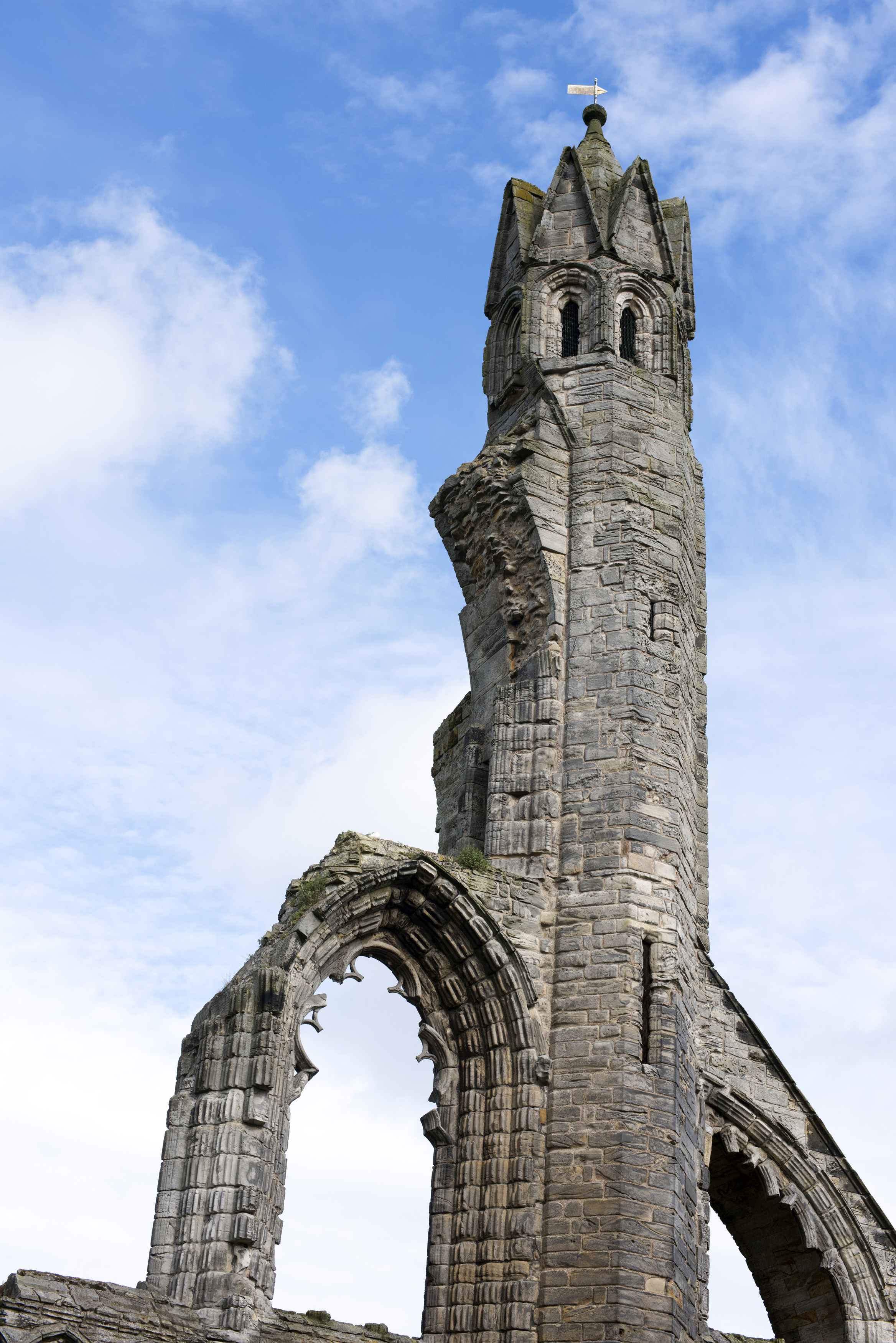 Low angle view on old stone carved tower of Saint Andrews Cathedral under partly sunny sky