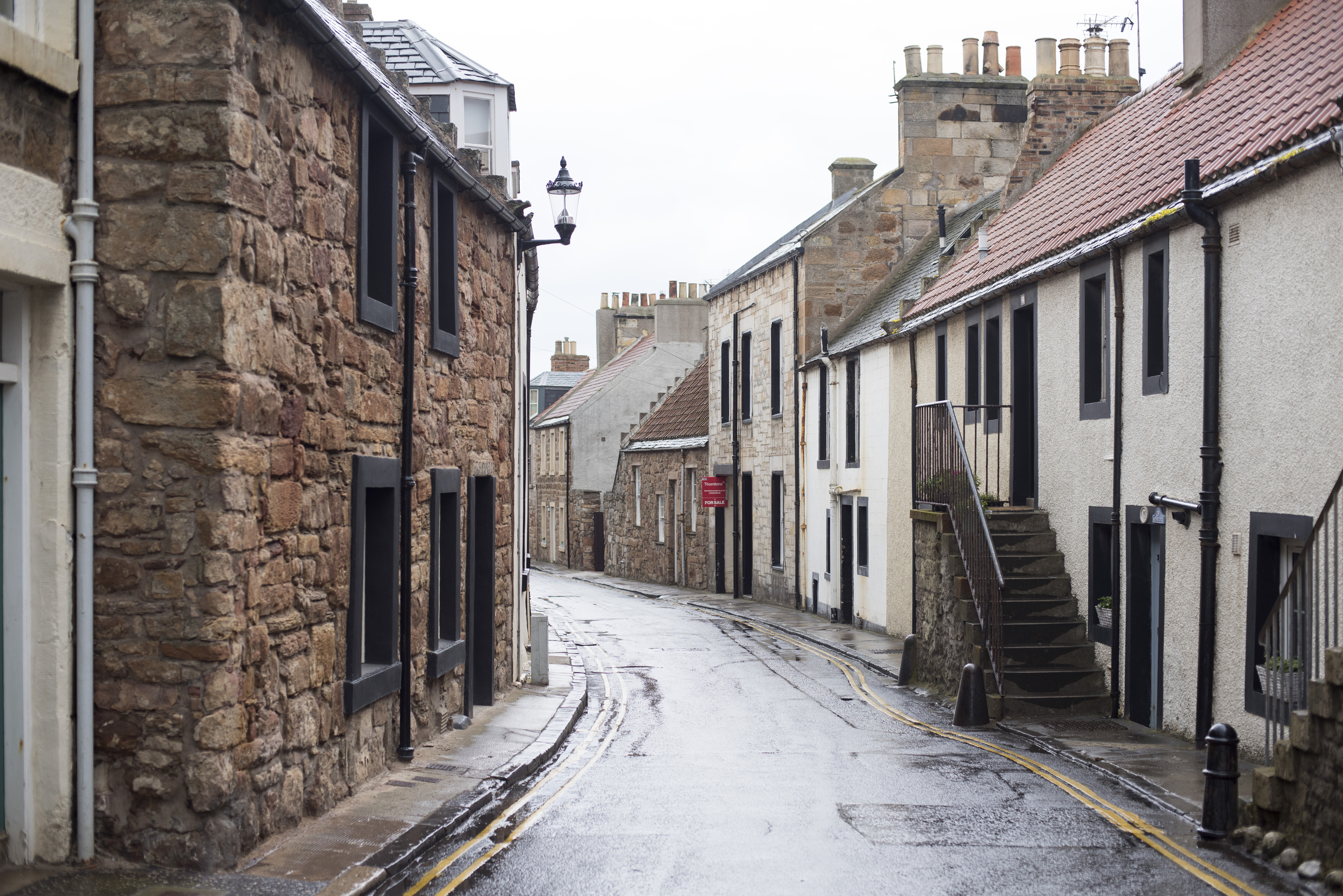 Narrow street in Cellardyke, Scotland lined with quaint cottages on a rainy overcast day