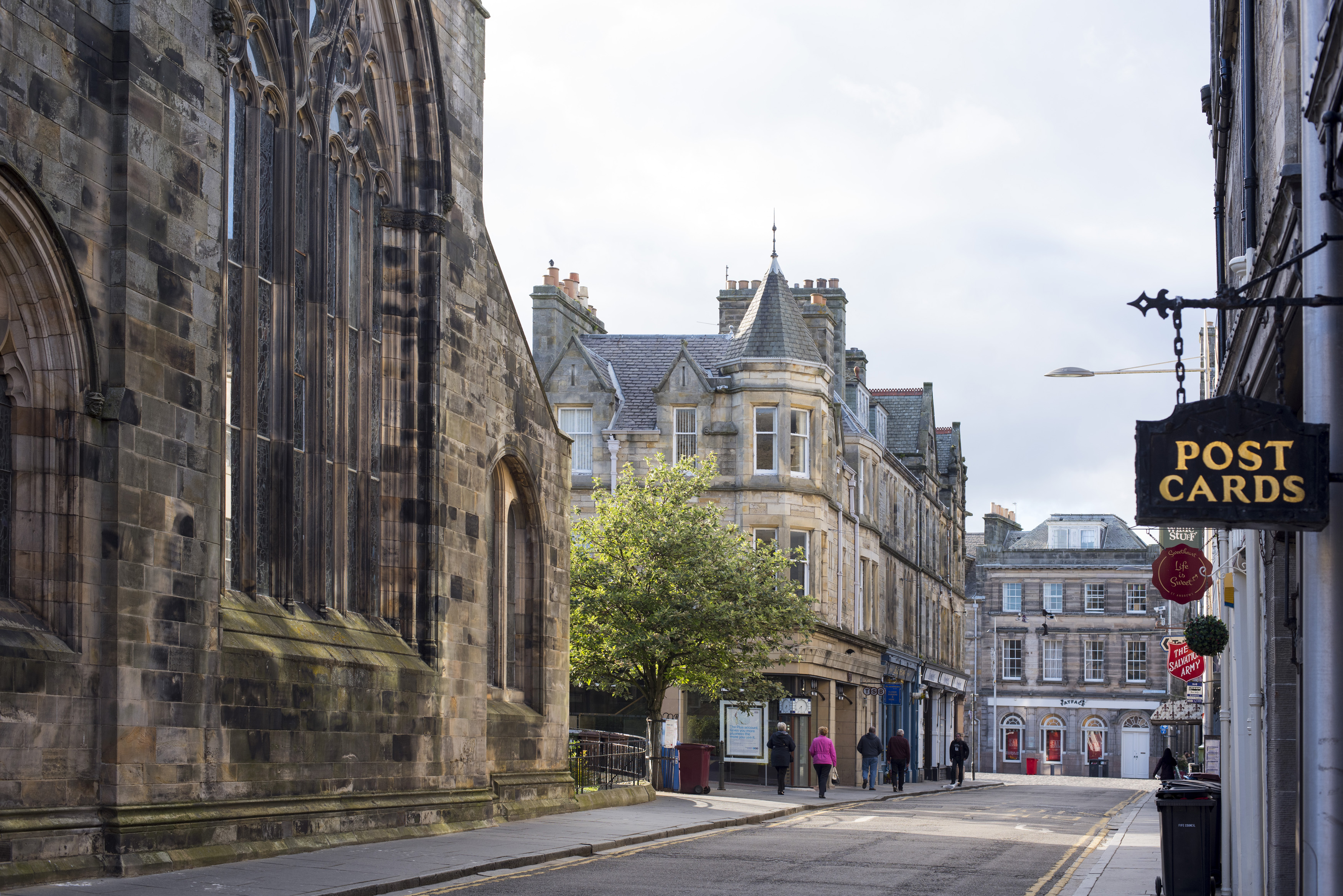 Street view in the historic town of St Andrews, Scotland showing the old stone architecture, church and businesses