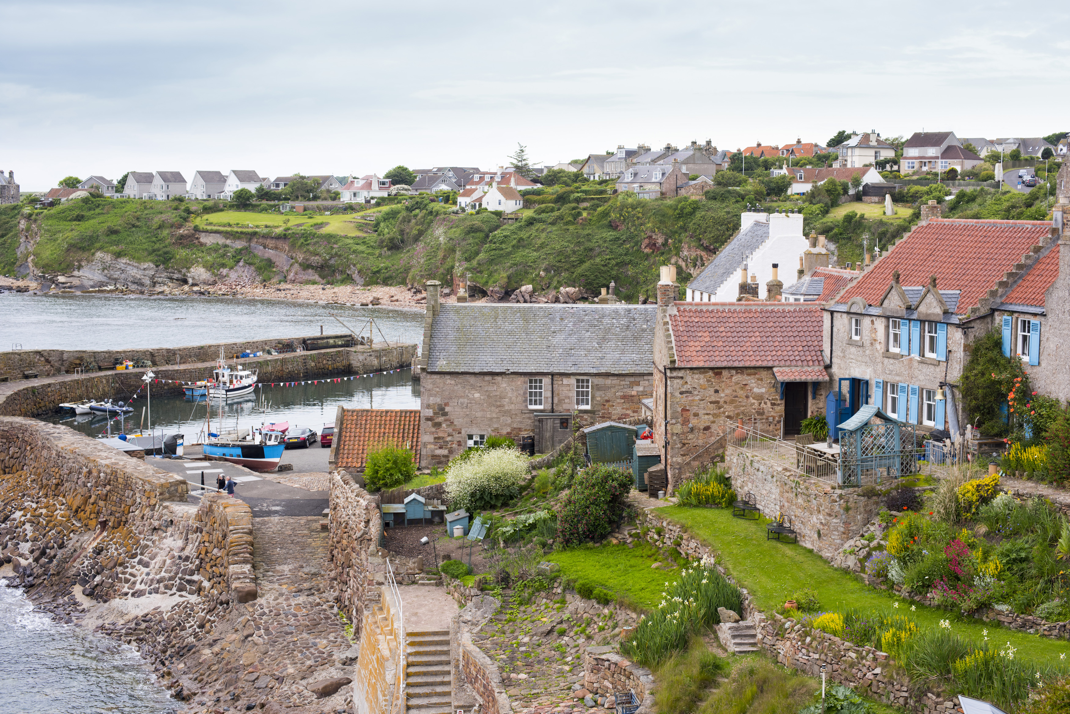 View of quaint houses, boats in bay and stairway down to water in Crail on the Fife Coast in Scotland