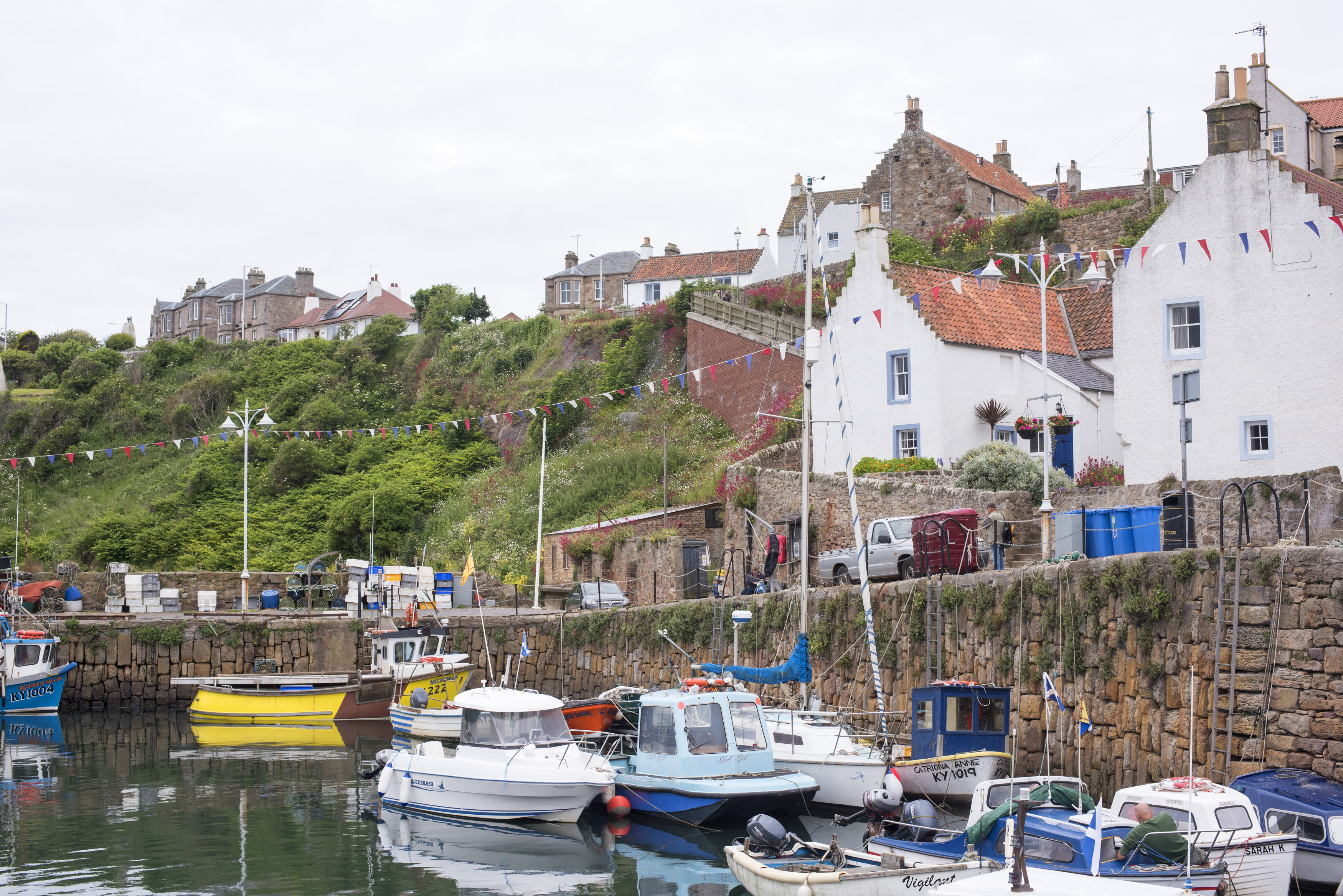 Waterfront view of small fishing boats moored at Crail, Scotland, a picturesque fishing village on the Fife coast