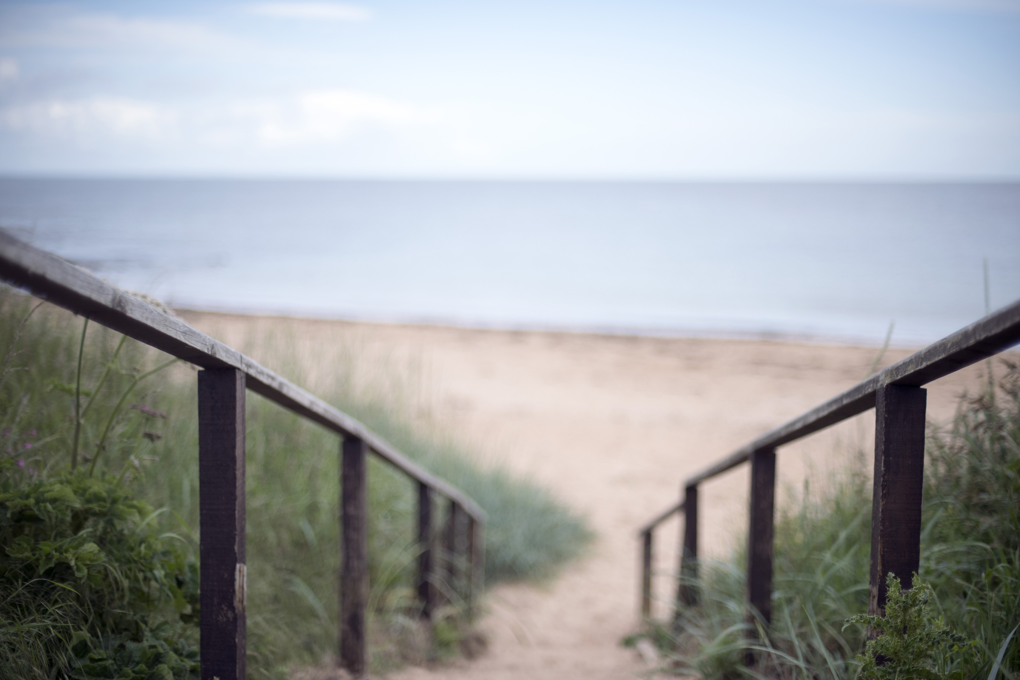 Stairs descending to the sandy beach and calm ocean on the Fife coast in Scotland, UK in a landscape view
