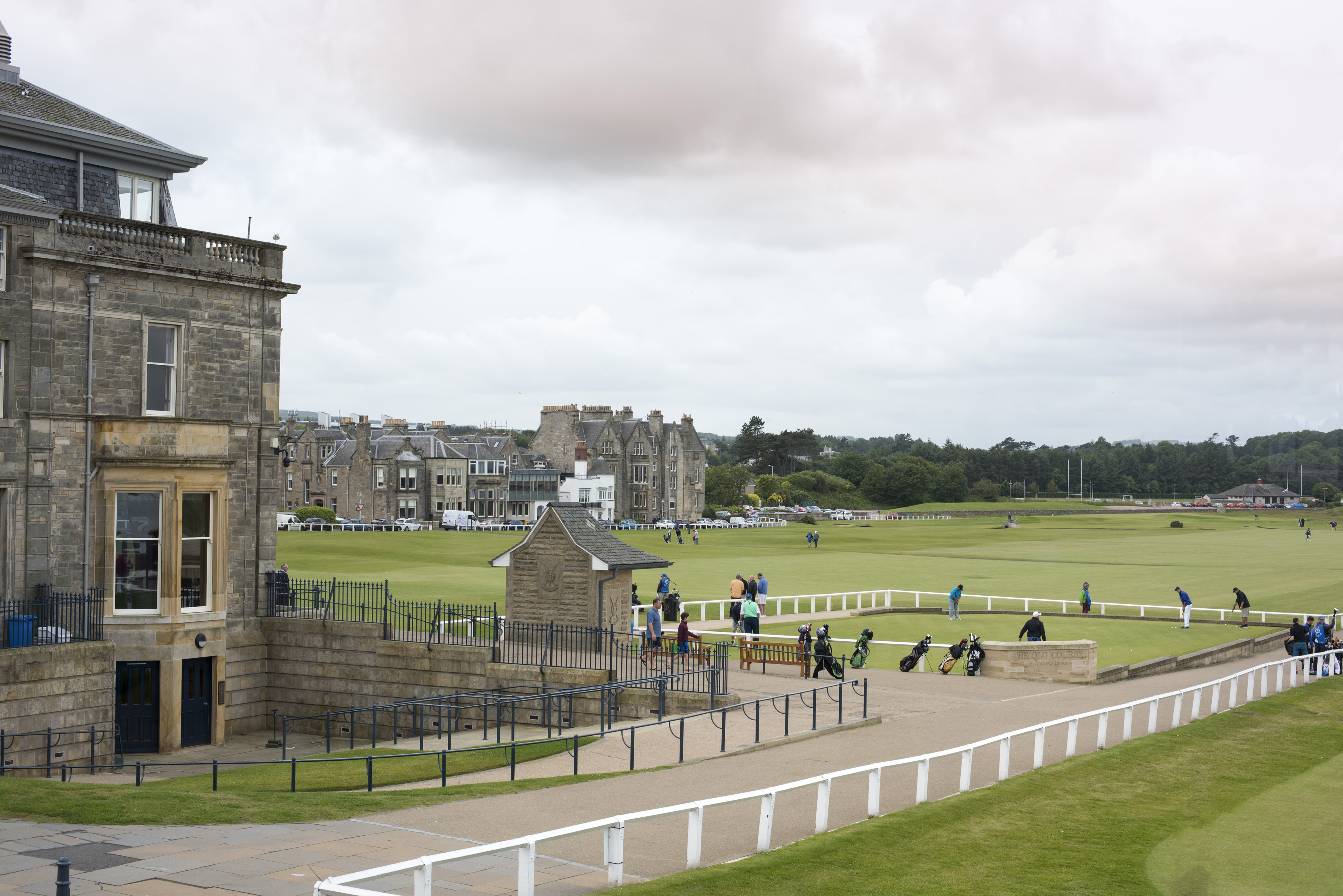 View of white fences and various golfers playing on golf green under overcast sky in Saint Andrews, Scotland