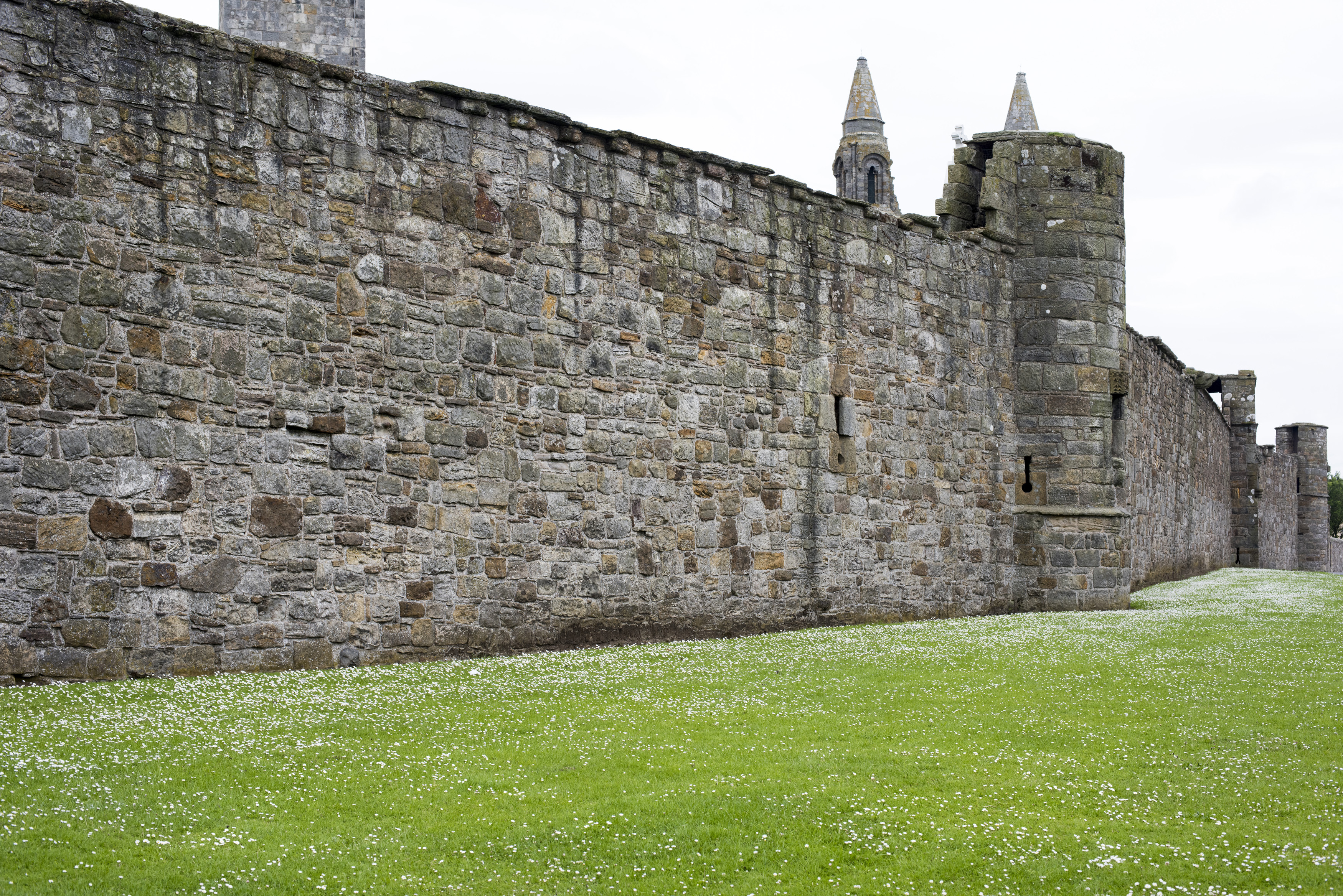 Ancient stone wall of the walled grounds of the St Andrews Cathedral ruins in the Scottish town of St Andrews in a receding perspective