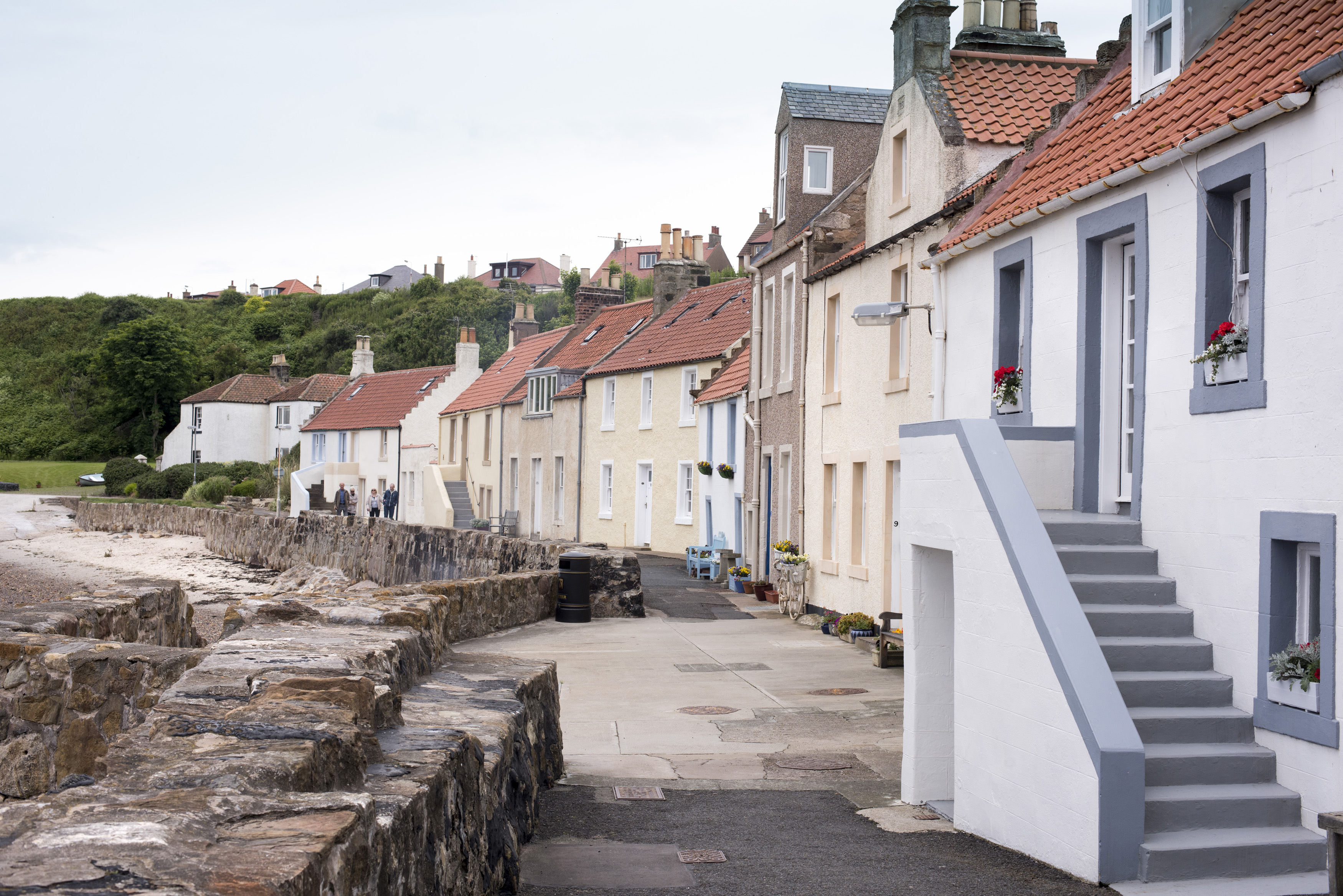 Large boulder seawall in front of historic old beach area houses at Pittenweem, Scotland