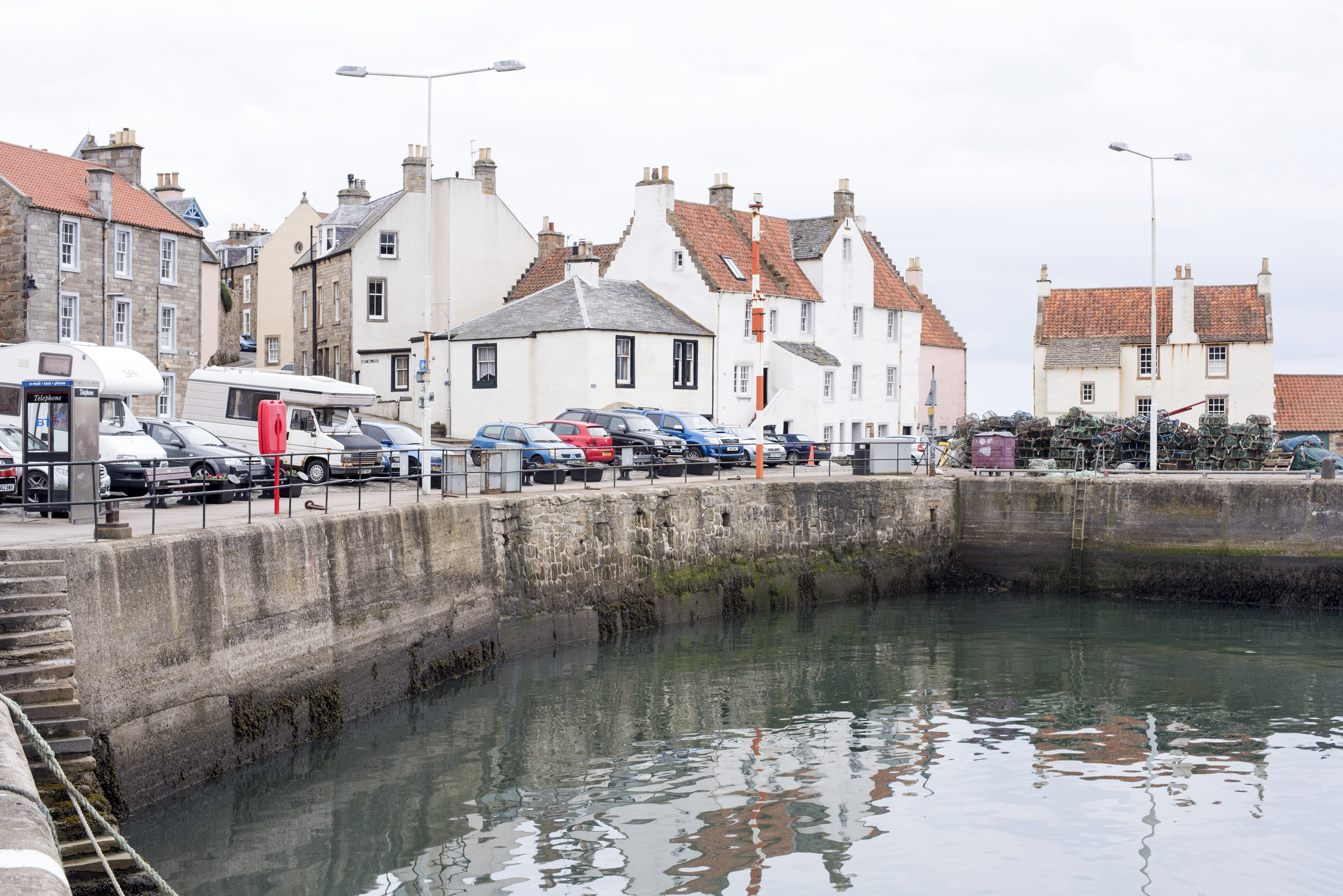 Cars and vans belonging to tourists parked around empty harbor at Pittenweem, Scotland