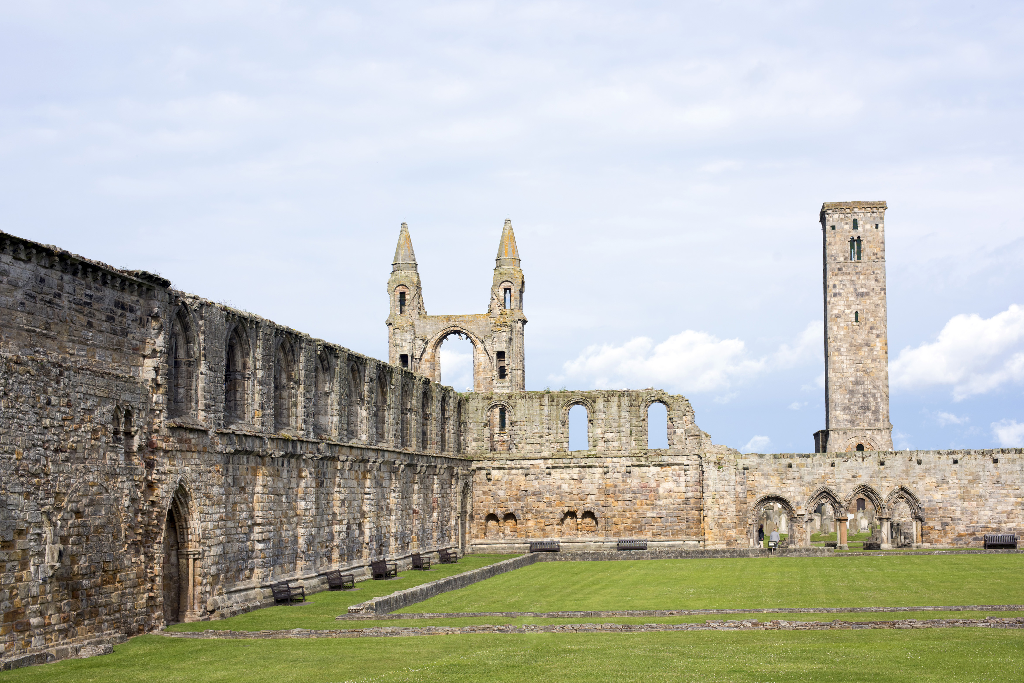 St Andrews Cathedral ruins, St Andrews, Scotland showing the remnants of the historic stone walls and Gothic spires under a cloudy grey sky