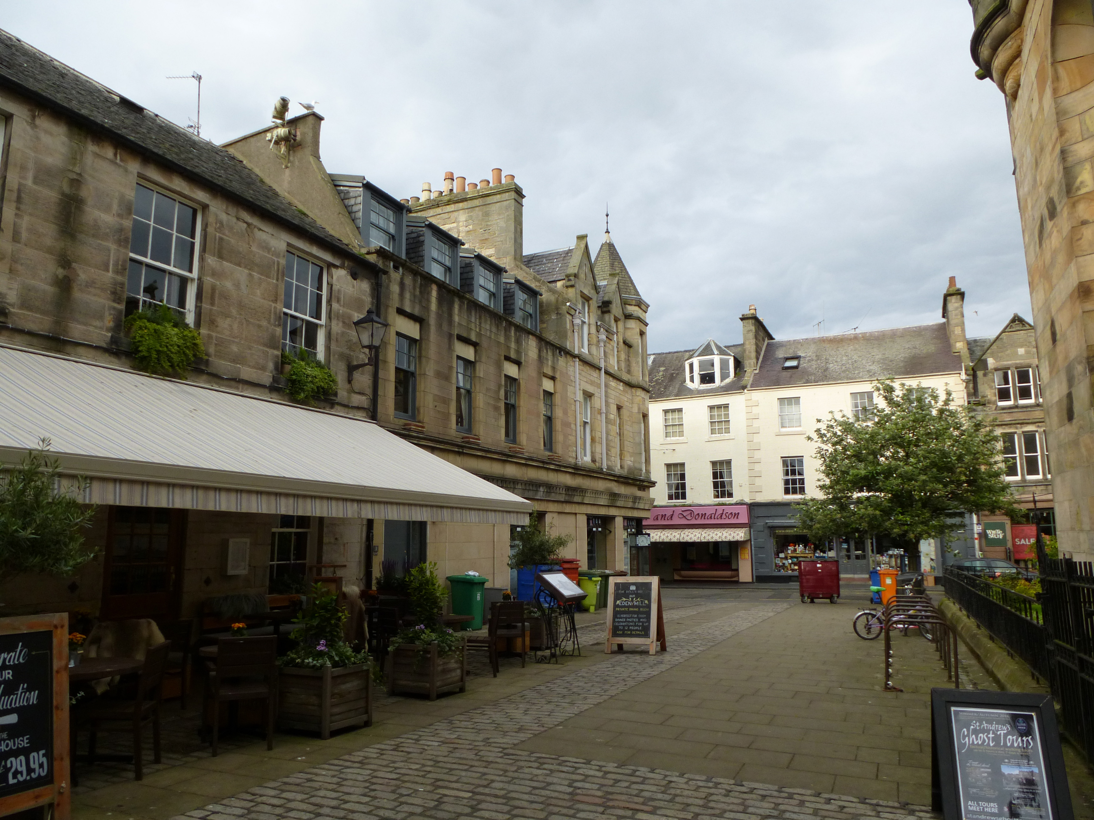 Open air restaurant on cobblestone street in quaint business area of Saint Andrews, Scotland