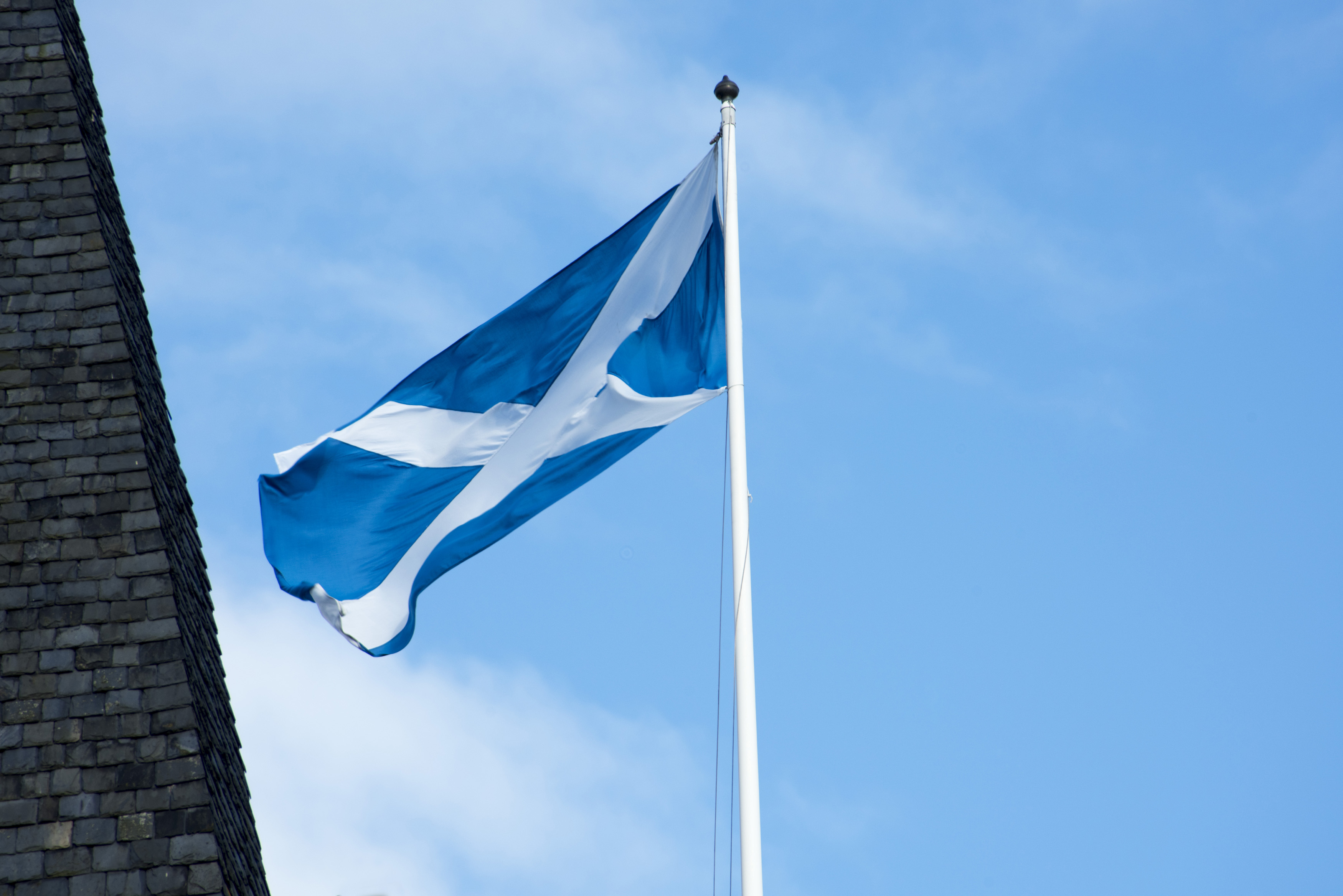 Scottish flag flying in St Andrews, Scotland fluttering in the wind on a white flagpole against a hazy blue sky