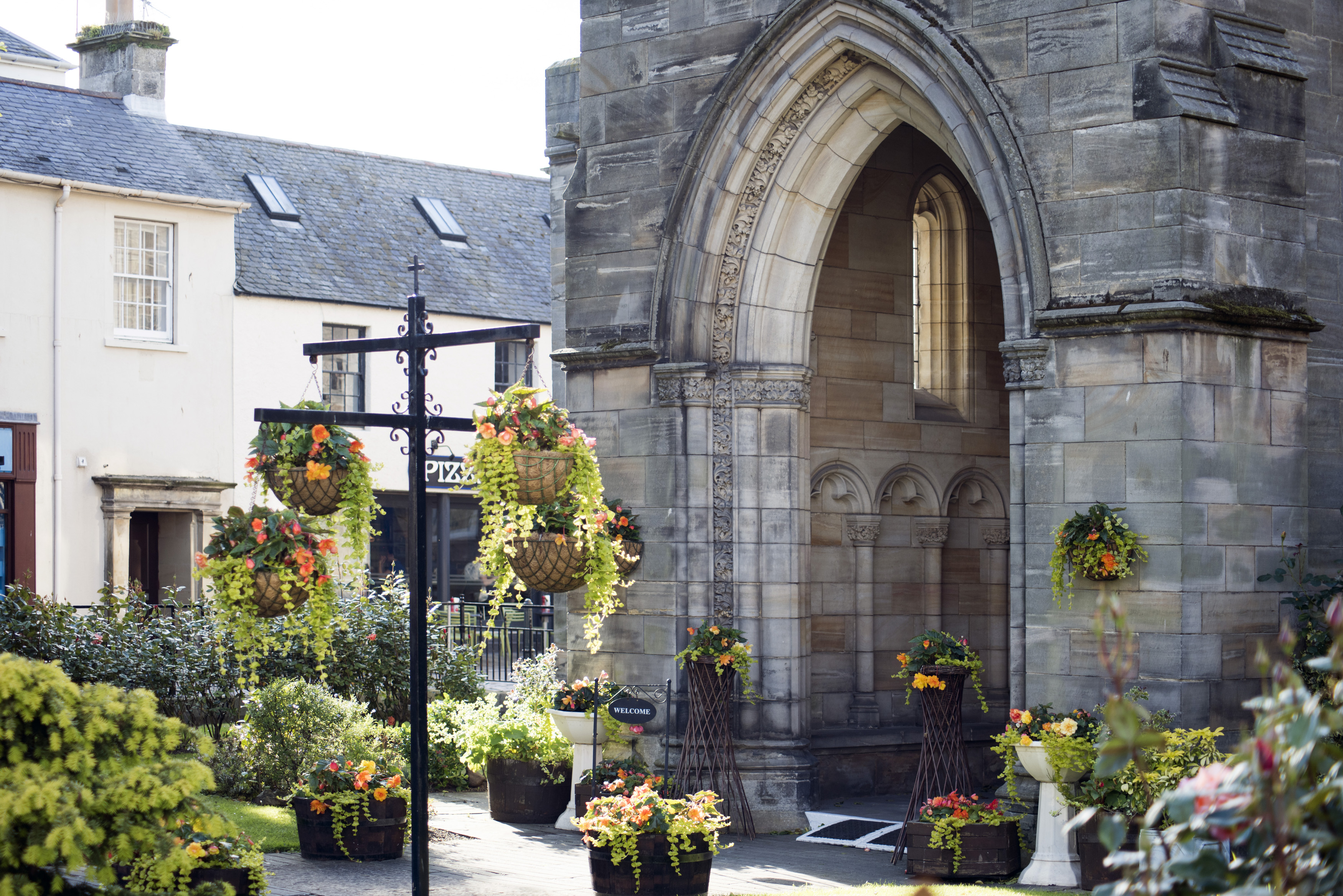 Flowing baskets near old stone church block entrance with arch in Saint Andrews, Scotland