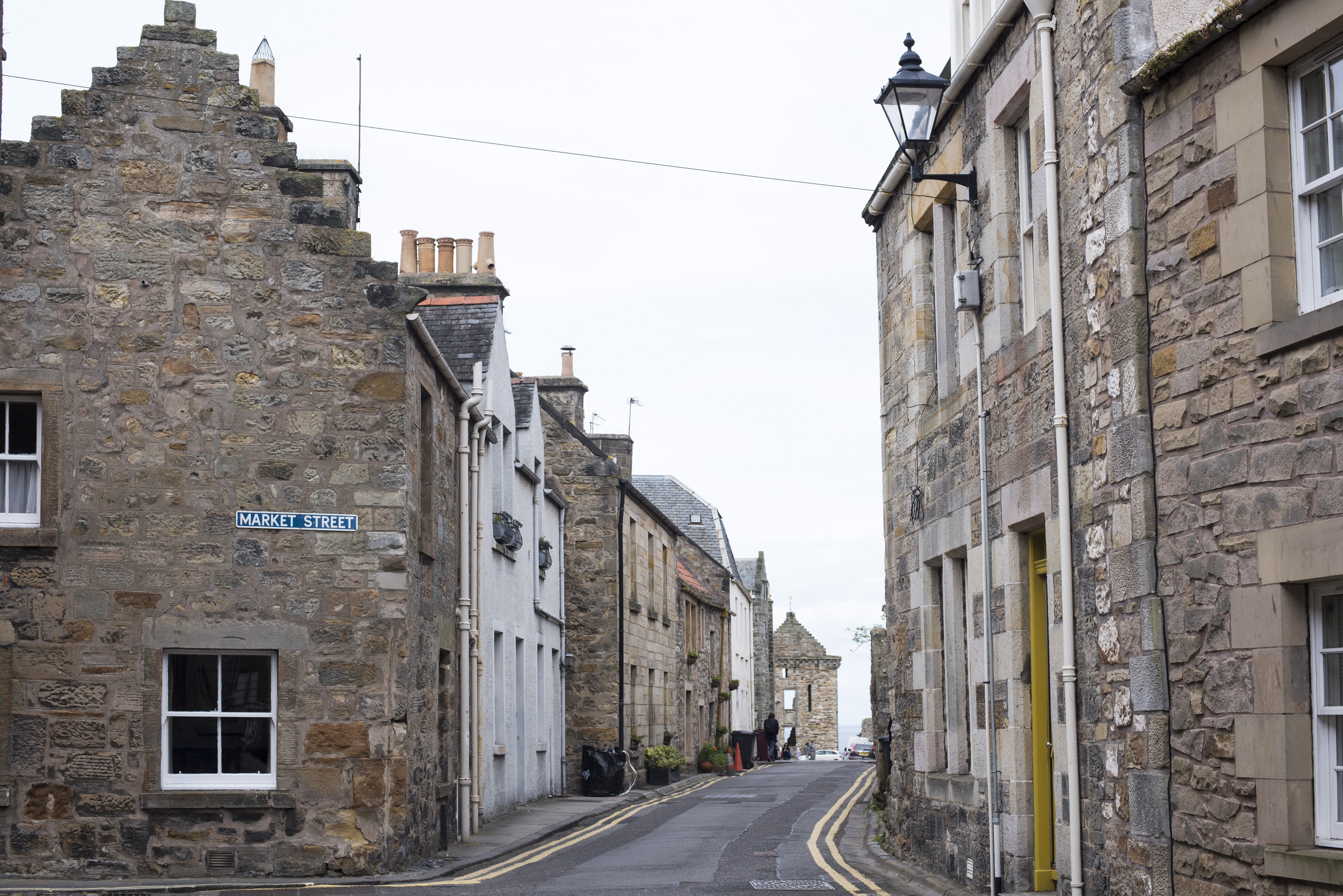 Two rows of old stone brick residential buildings on narrow road in Scotland near Saint Andrews