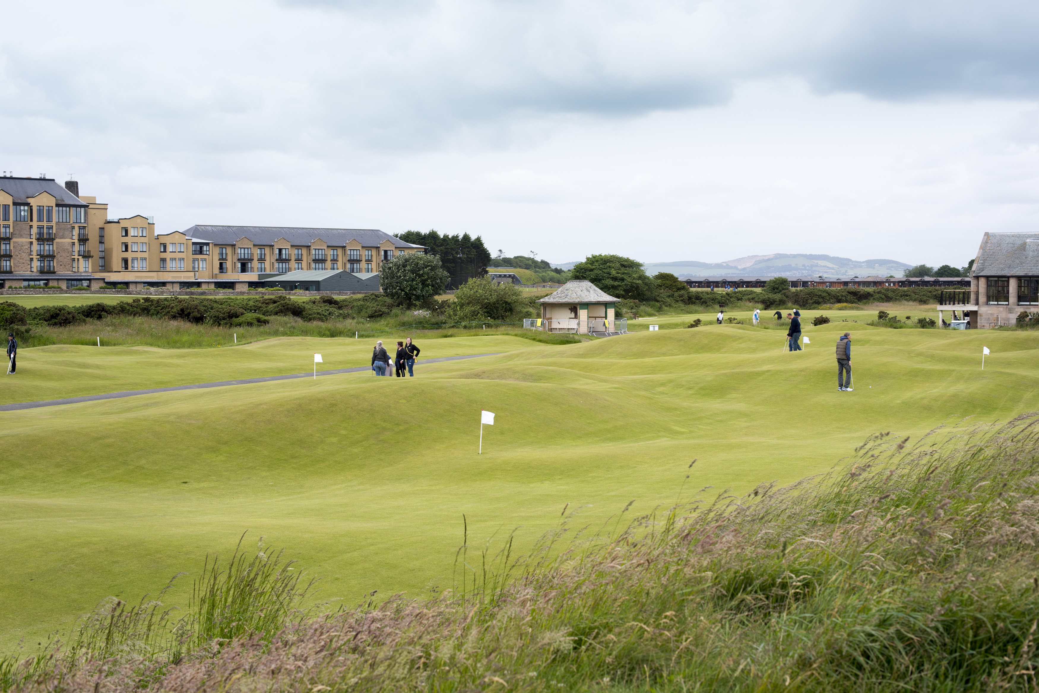 Golfers playing a round of golf on the course at St Andrews, Scotland with the clubhouse visible in the distance under a cloudy grey sky