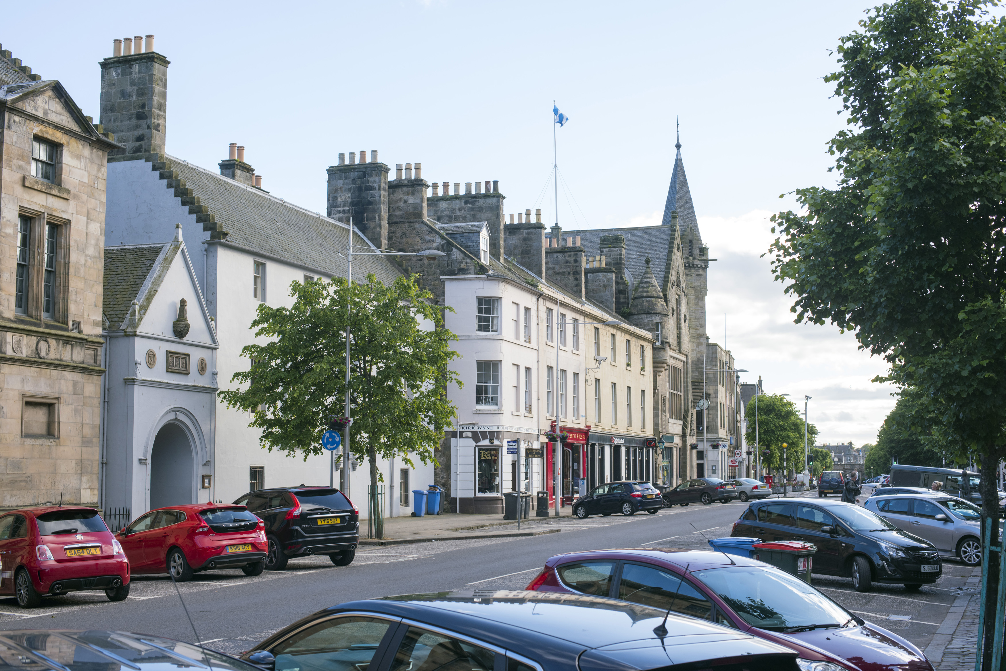 Street scene in St Andrews, Scotland with rows of parked cars in front of historic buildings on a quiet sunny day
