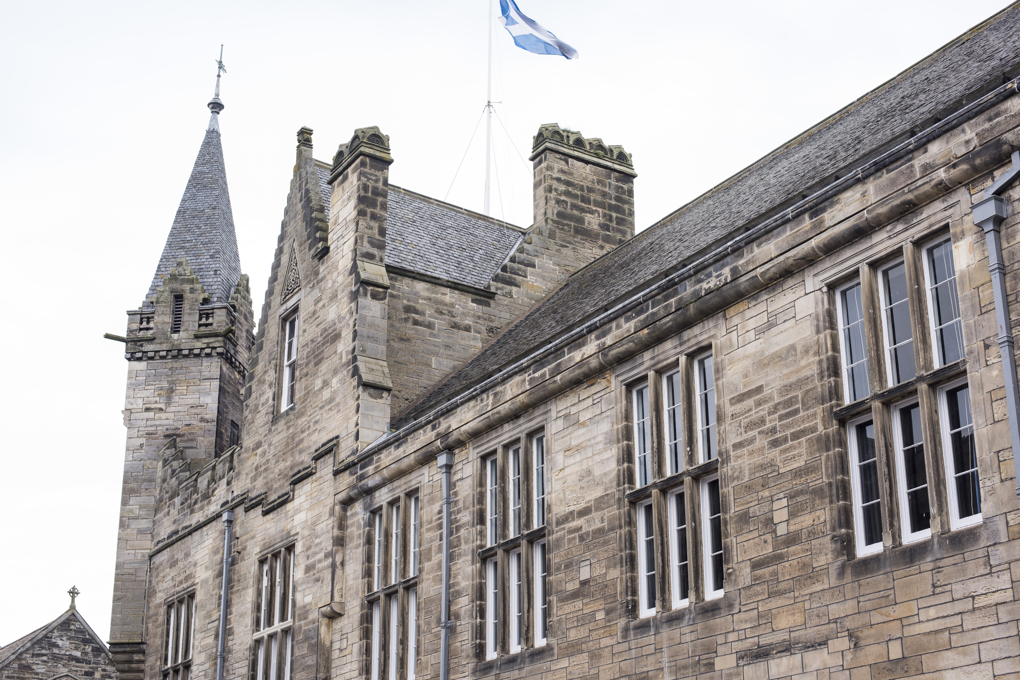 Close up of second floor of town hall with flag waving at top in Saint Andrews, Scotland
