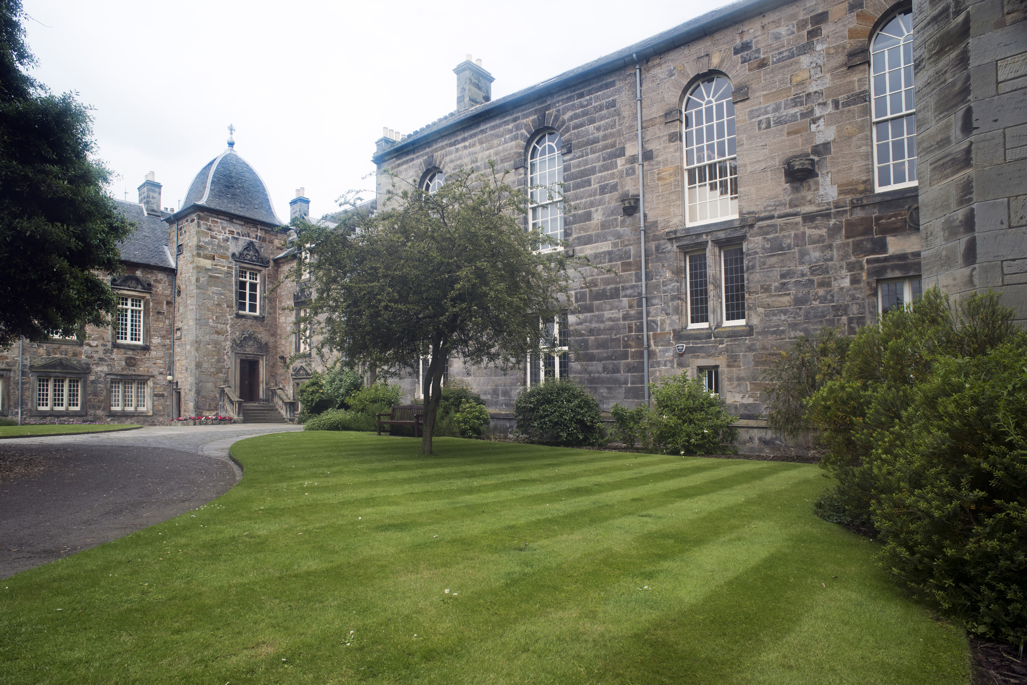 Grounds and historic buildings of St Andrews University, Scotland showing manicured lawns and old stone architecture with graceful arched windows