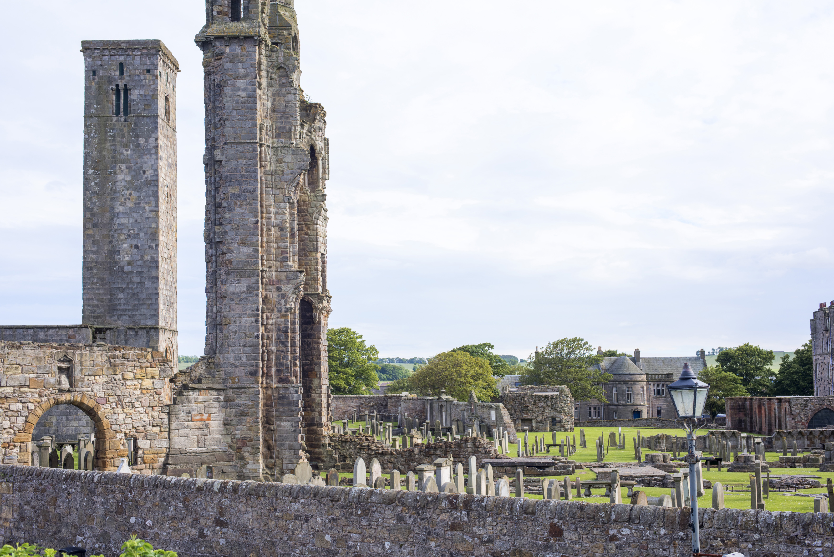 Stone barrier in front of old graveyard and towers of Saint Andrews Cathedral in Scotland with copy space in sky