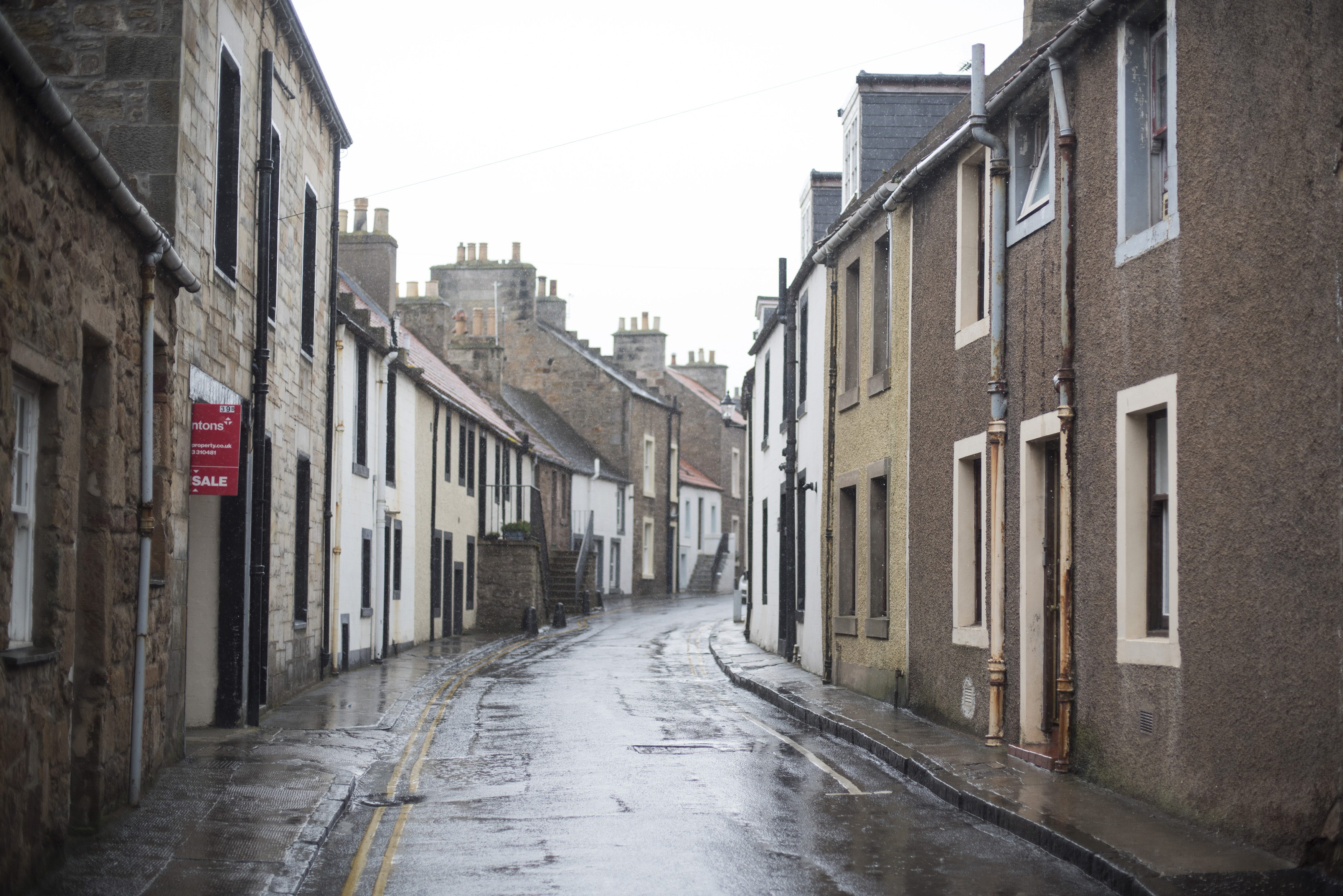 Lovely Scottish village as rain falls on street lined with pretty row homes