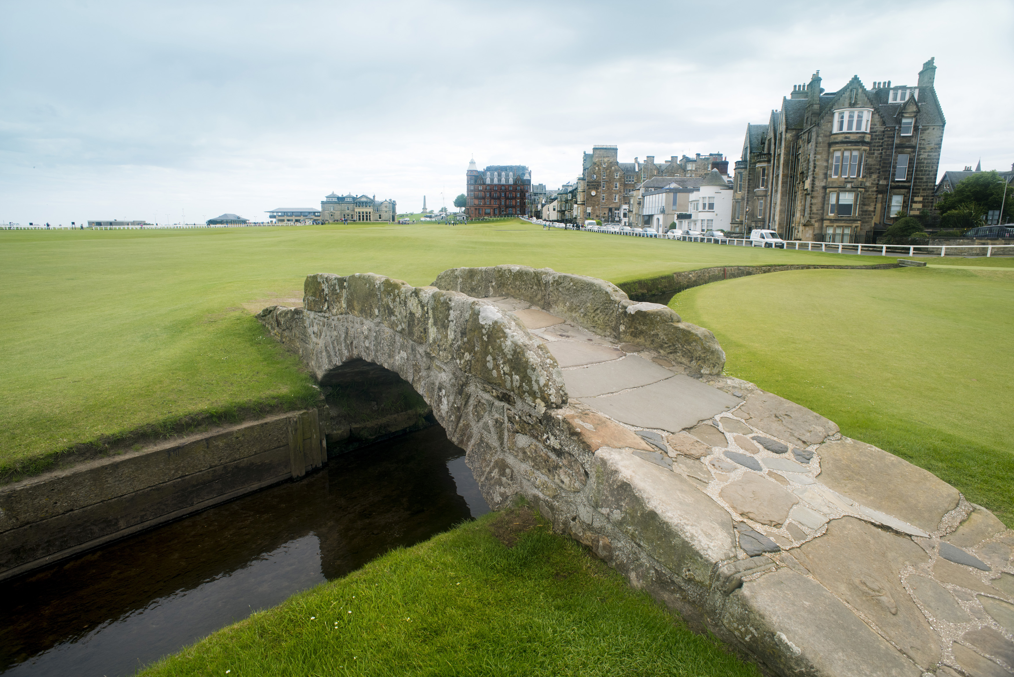 Green grass covered golf course with little stone Swilken bridge in Saint Andrews, Scotland