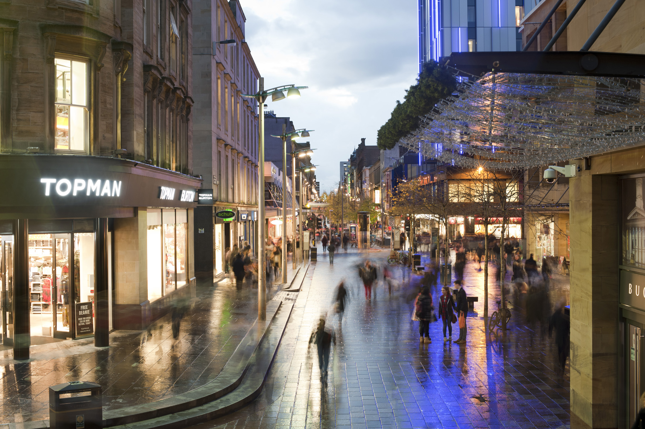 Sauchiehall Street in Glasgow is one of the main commercial streets in the city centre viewed here at night with pedestrians walking past illuminated shop fronts