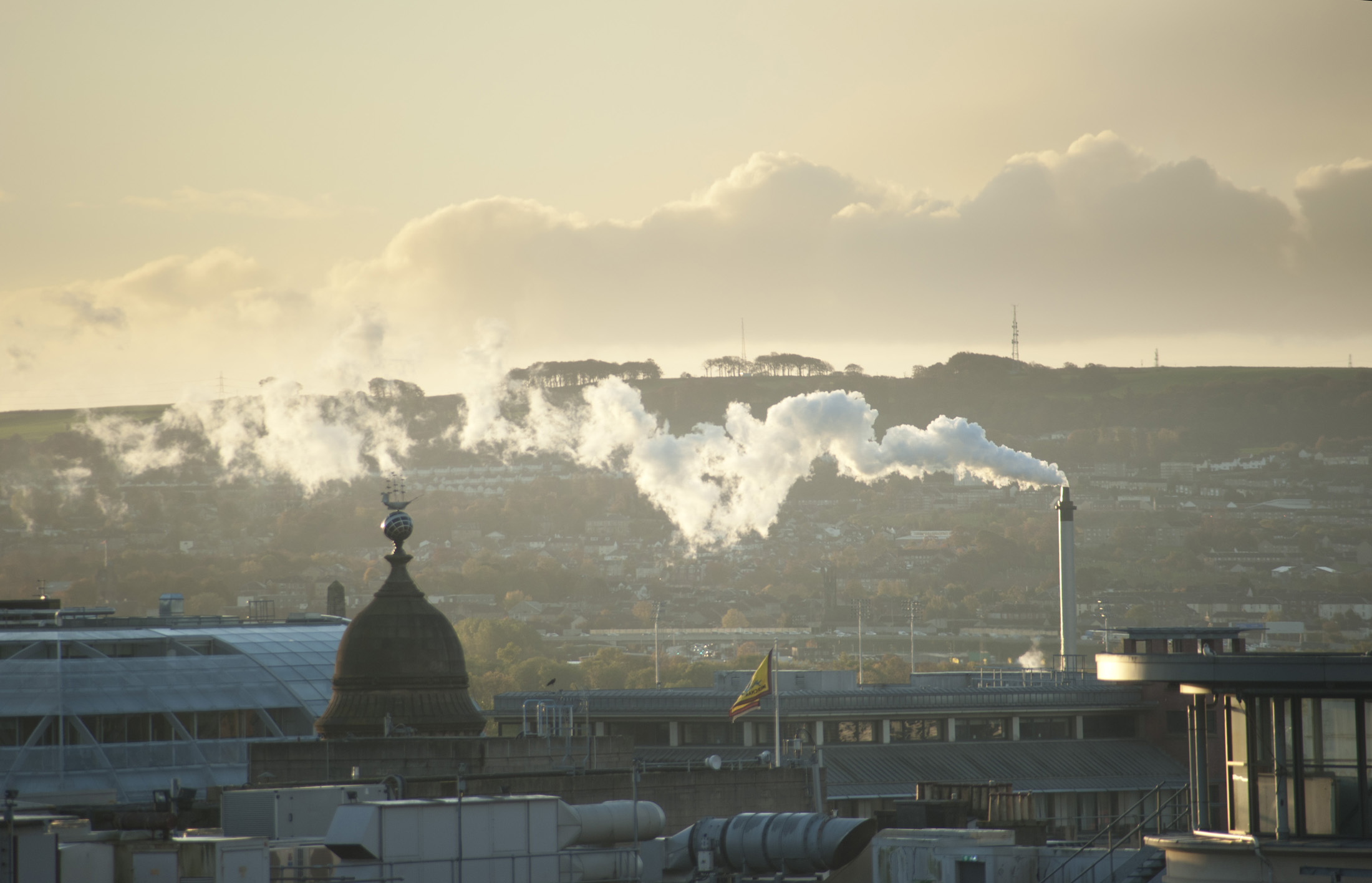 Industrial chimney belching smoke in Glasgow as it wafts across a misty smoggy city skyline polluting the atmosphere