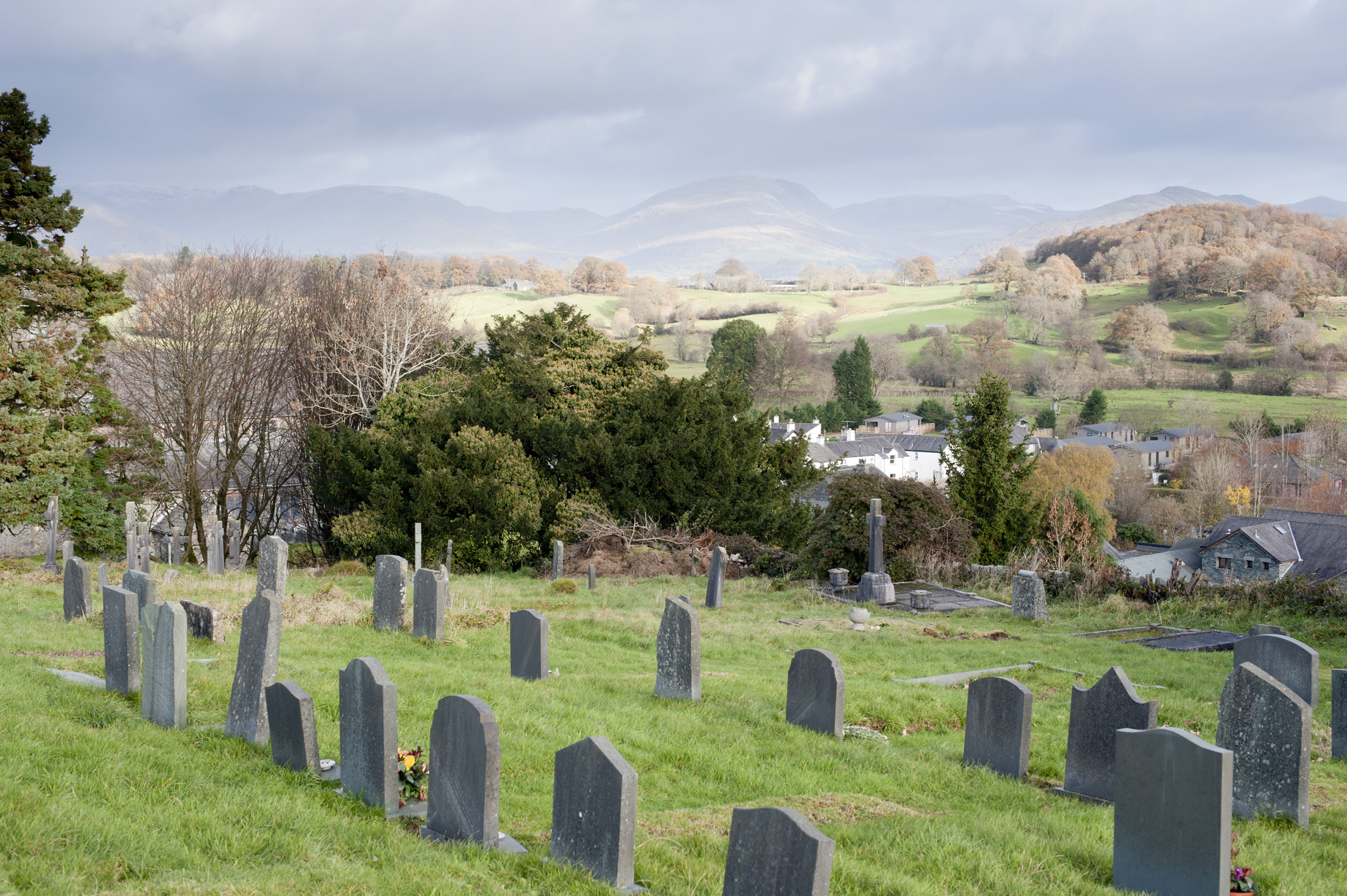 Gravestones in the churchyard at Hawkshead in the English Lake District with a view to beautiful lush green countryside and hills beyond