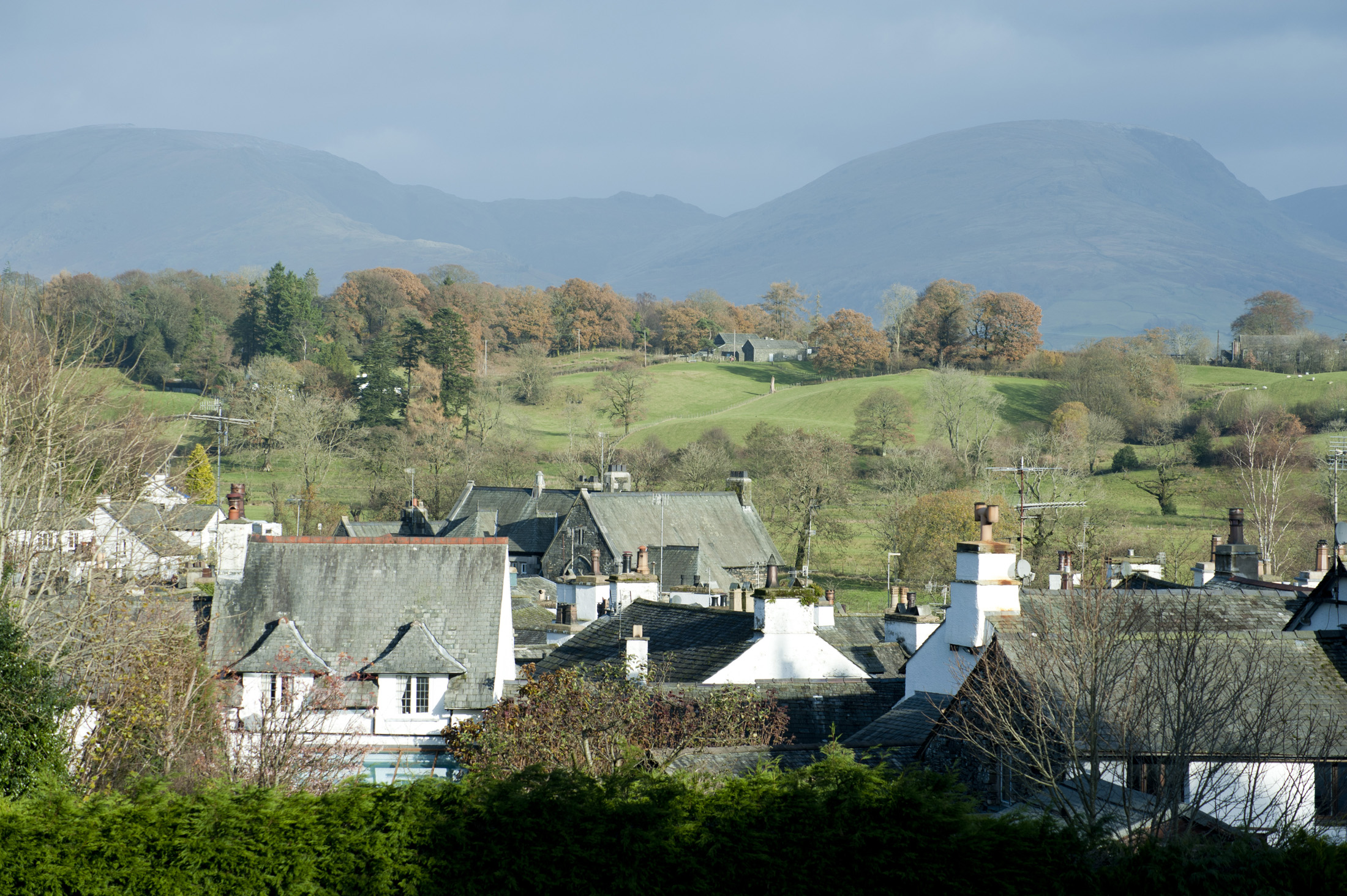 View over the rooftops of the whitewashed cottages of Hawkshead village to Red Screes in the English Lake District in Cumbria