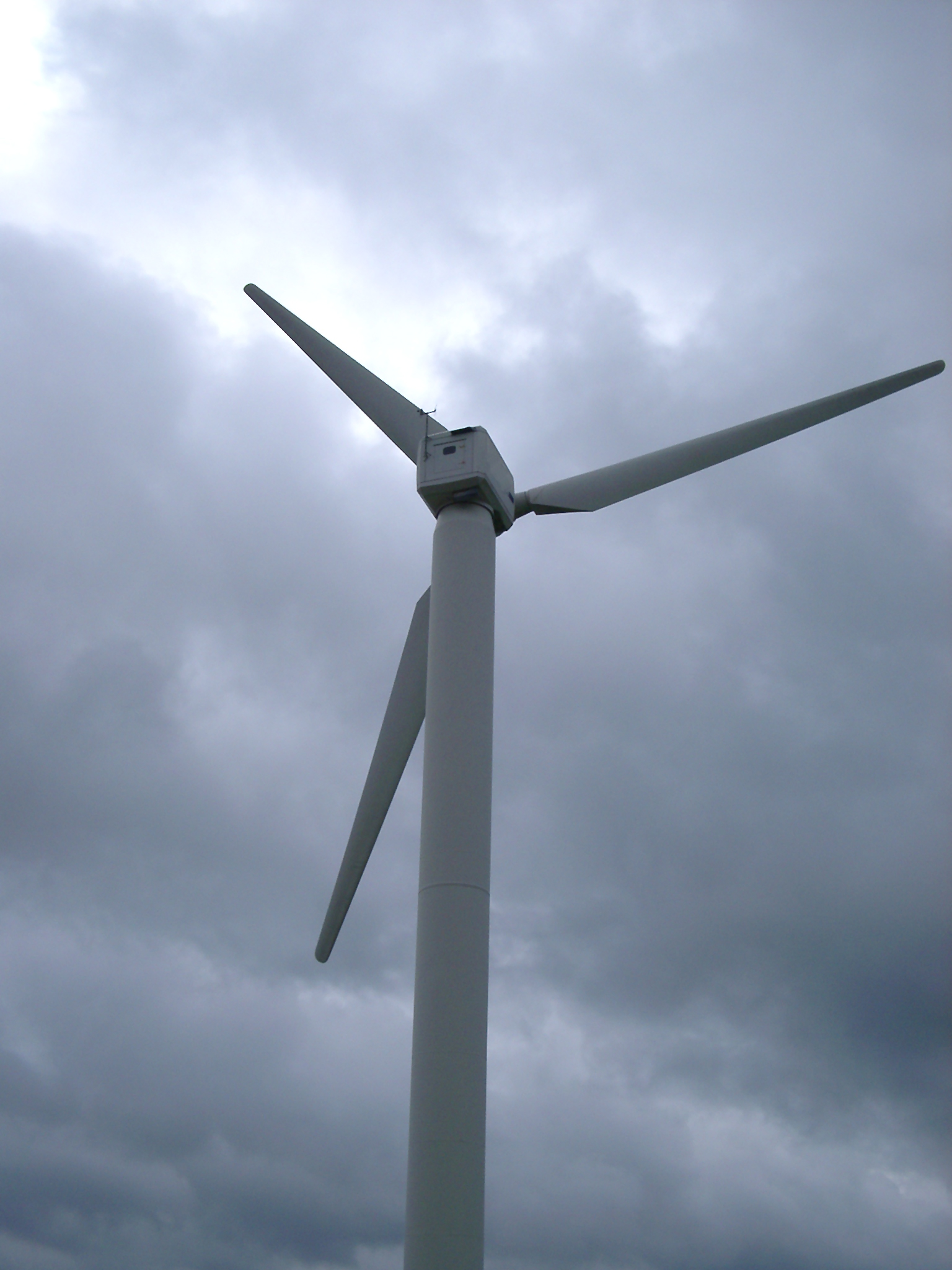 a wind turbine against a stormy sky over a cumbiran fell