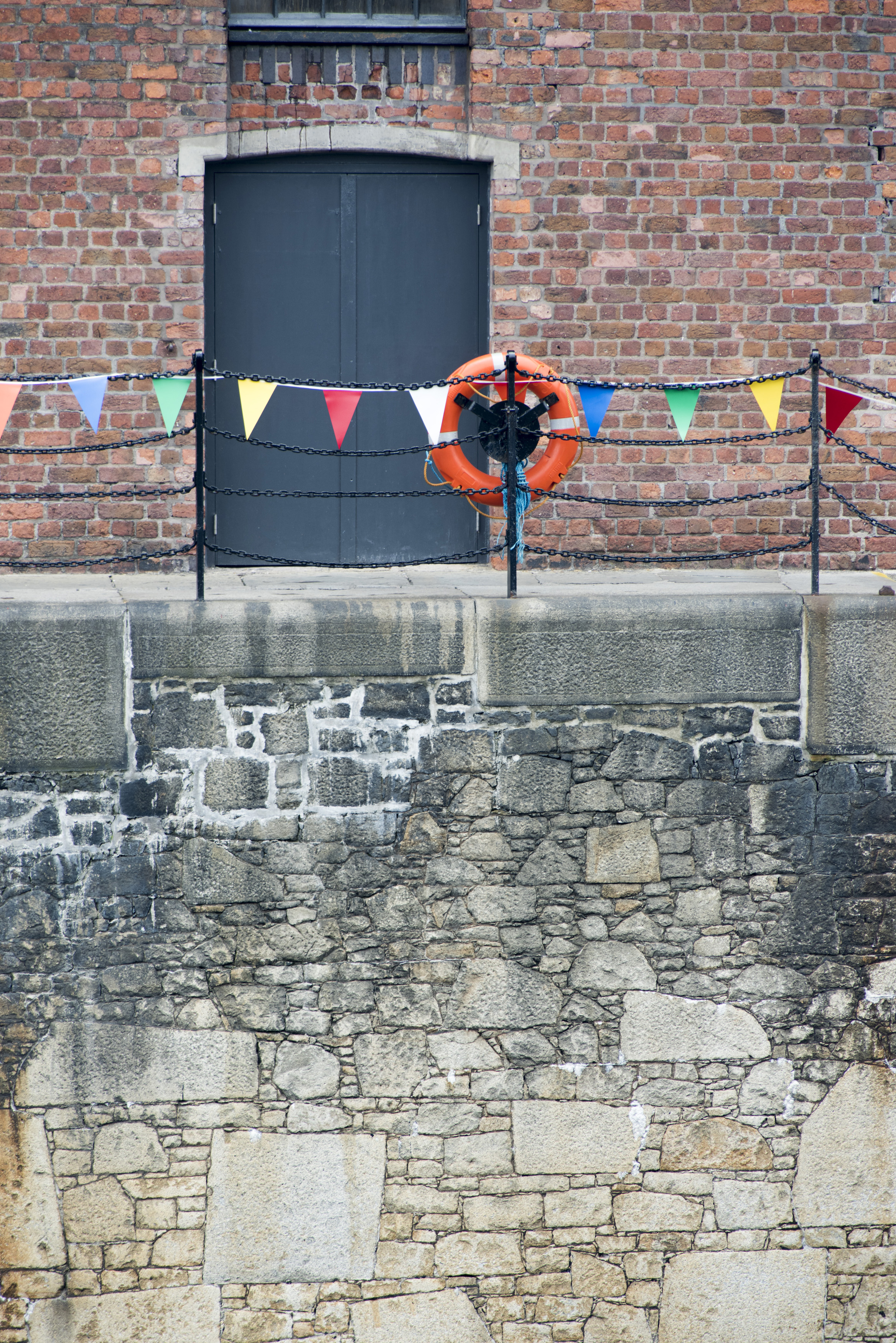 Orange life preserver on iron pole and chain railing at Liverpool Albert Dock with locked black doors surround by brick wall